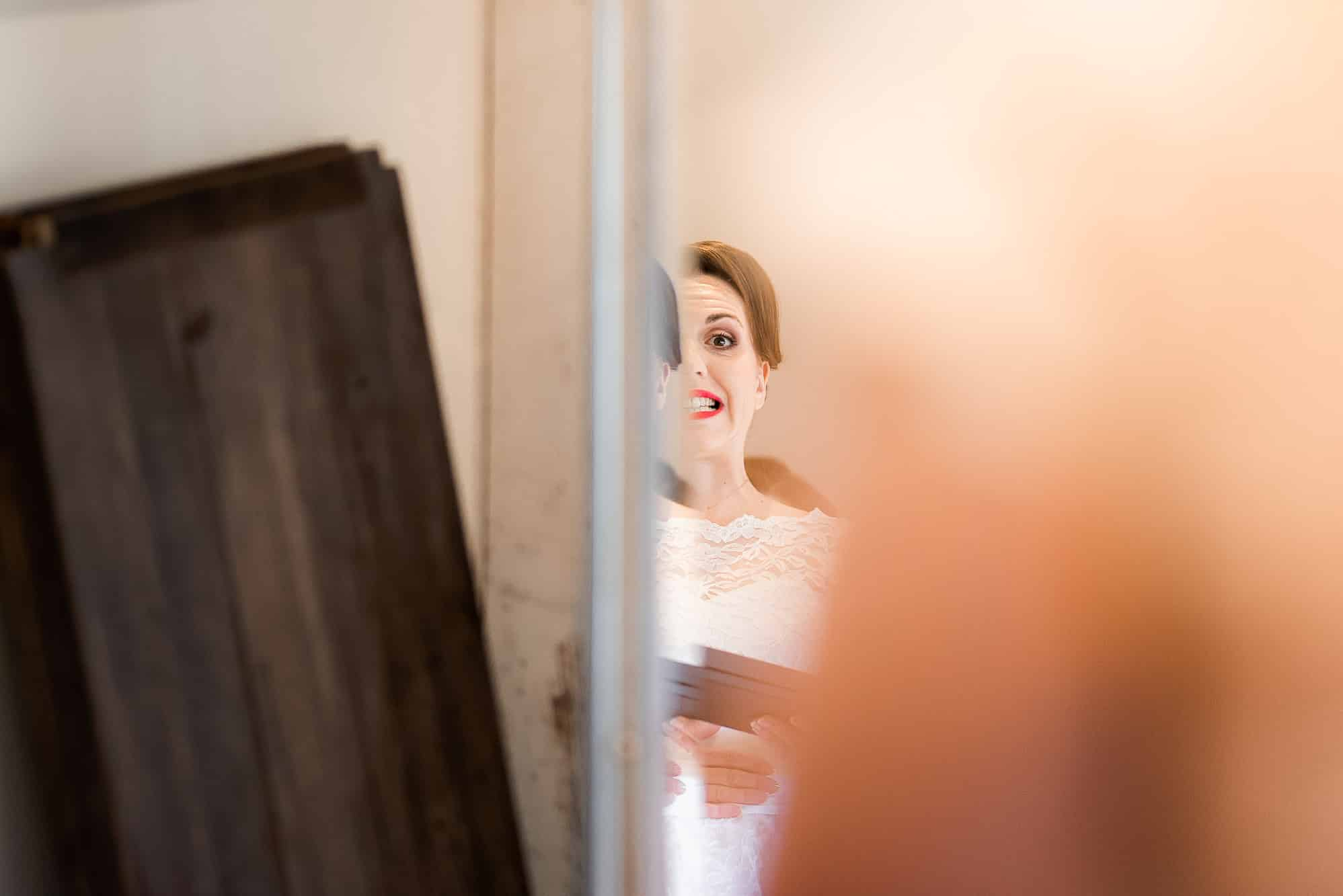 Bride in her dress and looking in mirror
