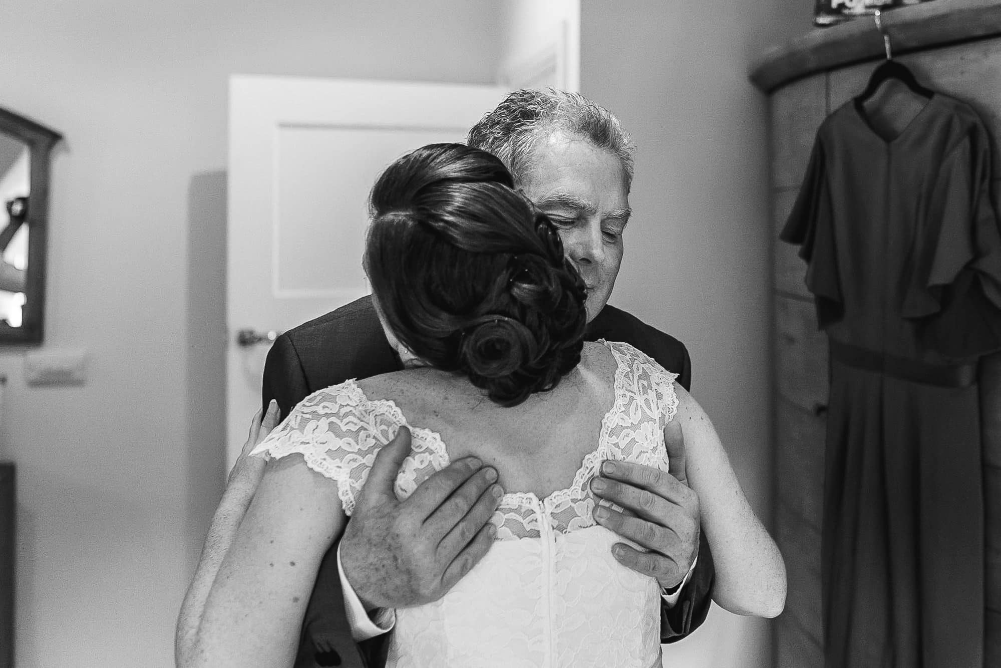 Dad hugging his daughter who is the bride