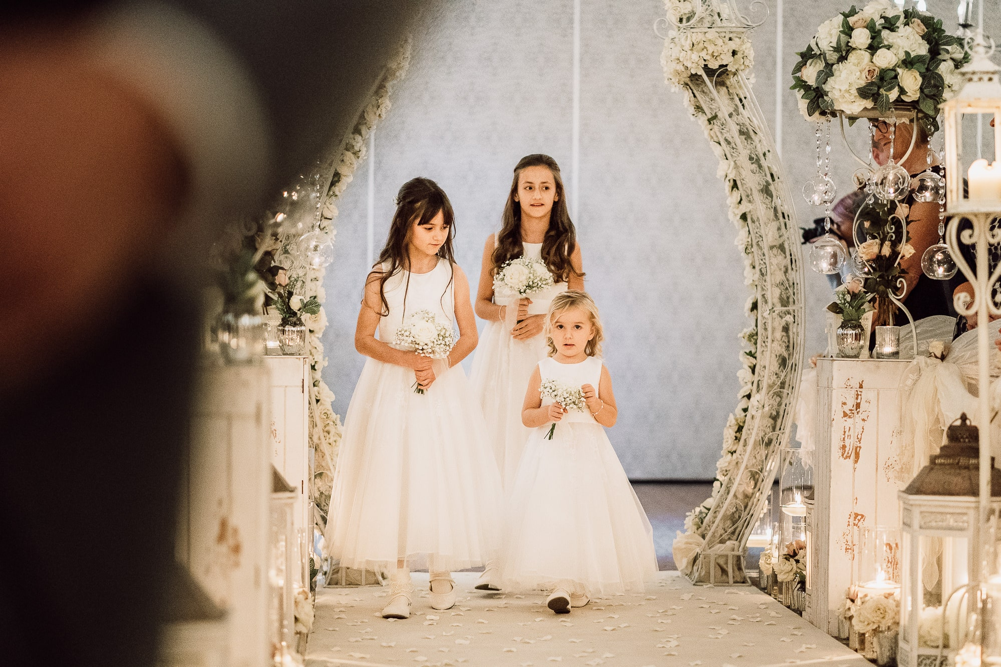 Flower girls walking down the aisle at Mottram Hall