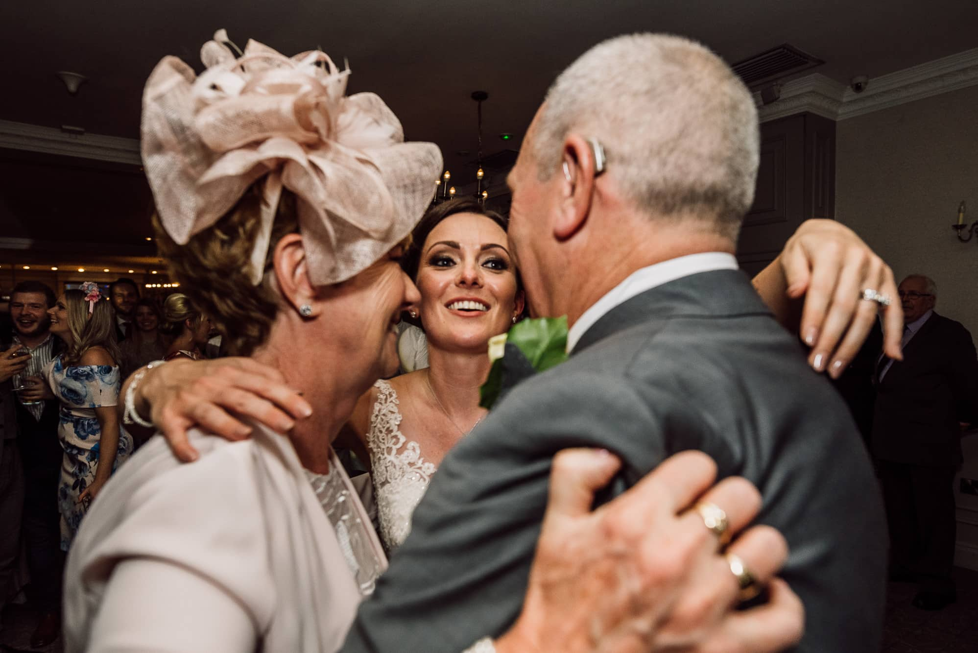 Bride dancing and hugging her mum and dad at Mottram Hall