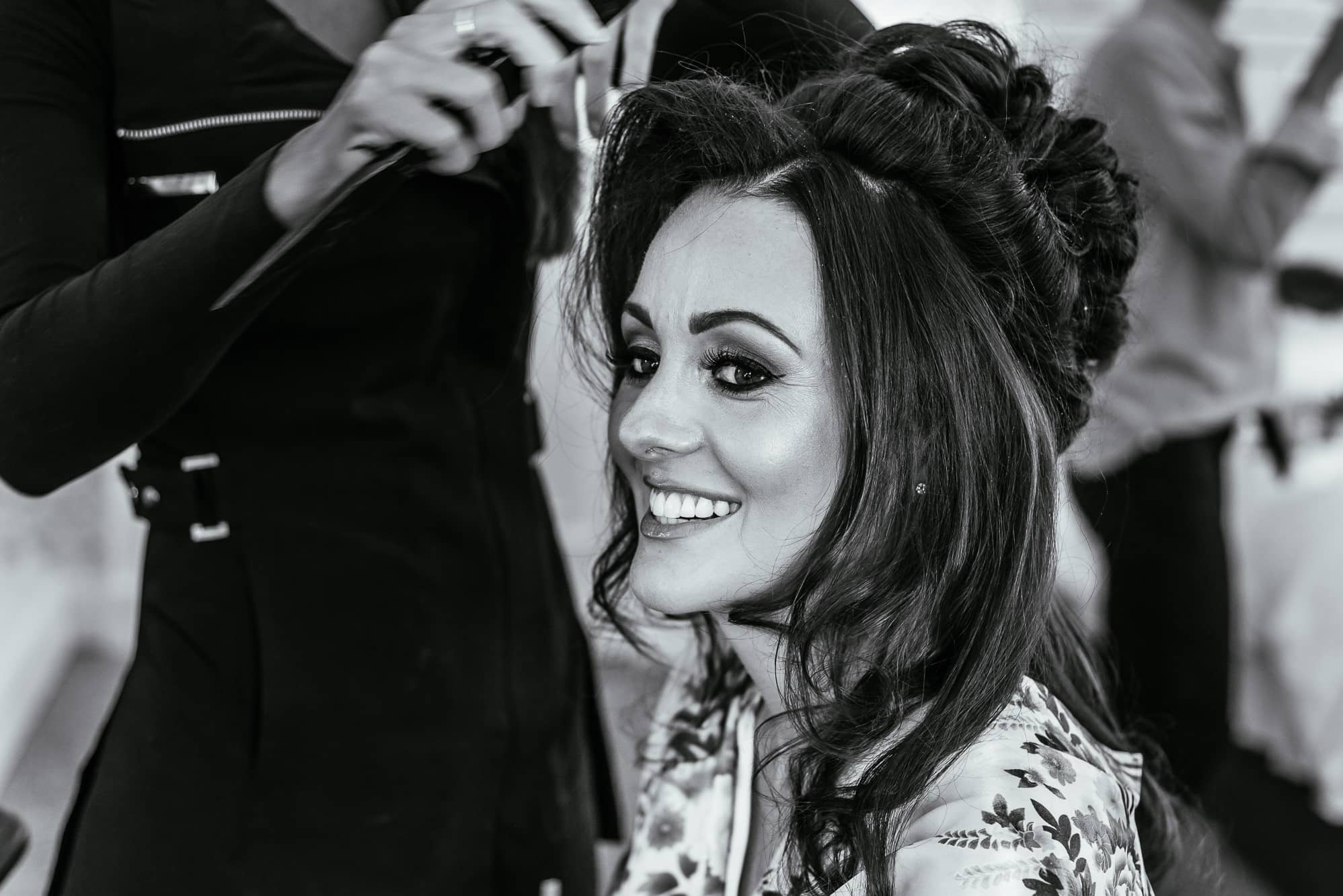 Bride smiling as her hair is done at Mottram Hall