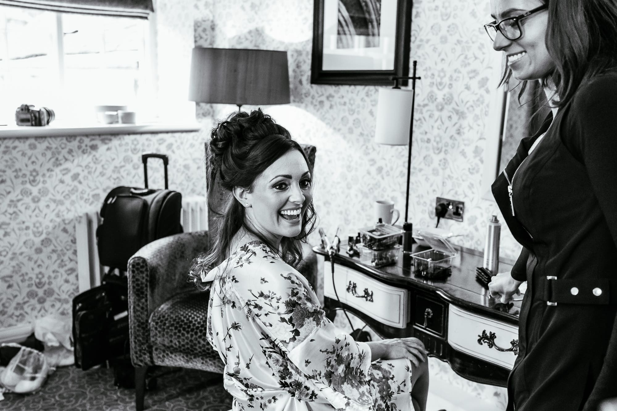 Bride laughing as she is having her make up done