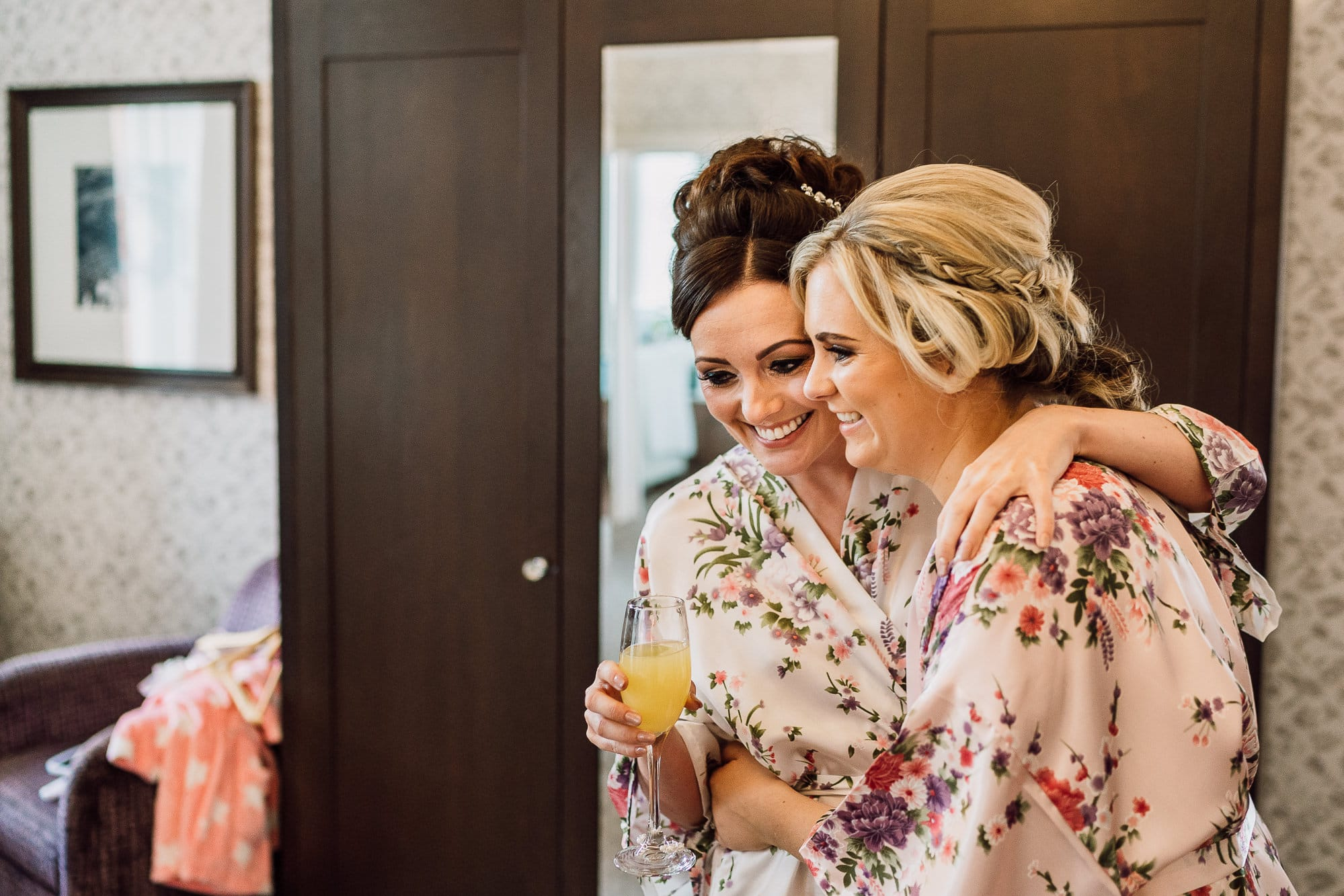 Bride to be hugging her bridesmaid at Mottram Hall during bridal preparation