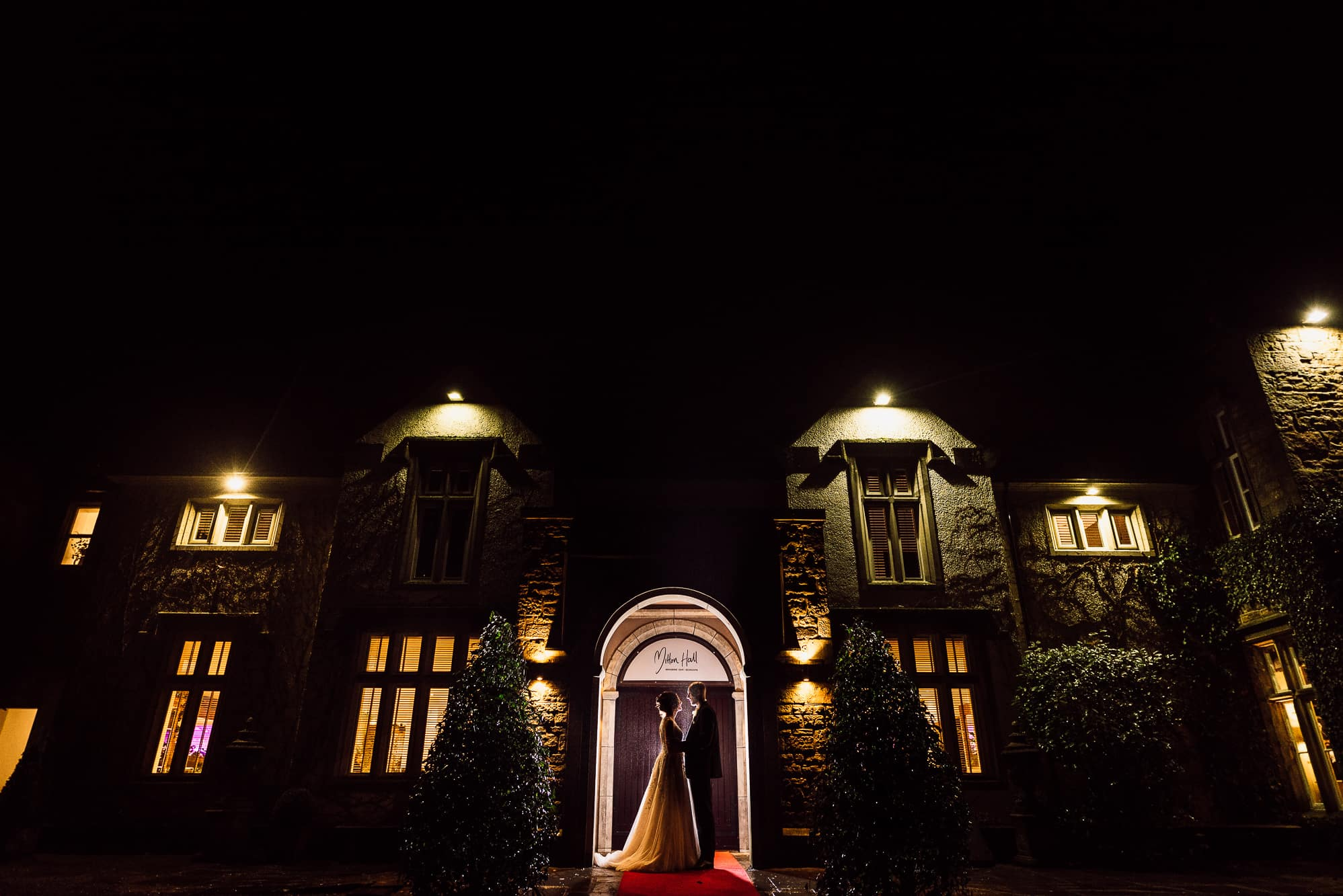 Photo of the bride and groom outside mitton hall