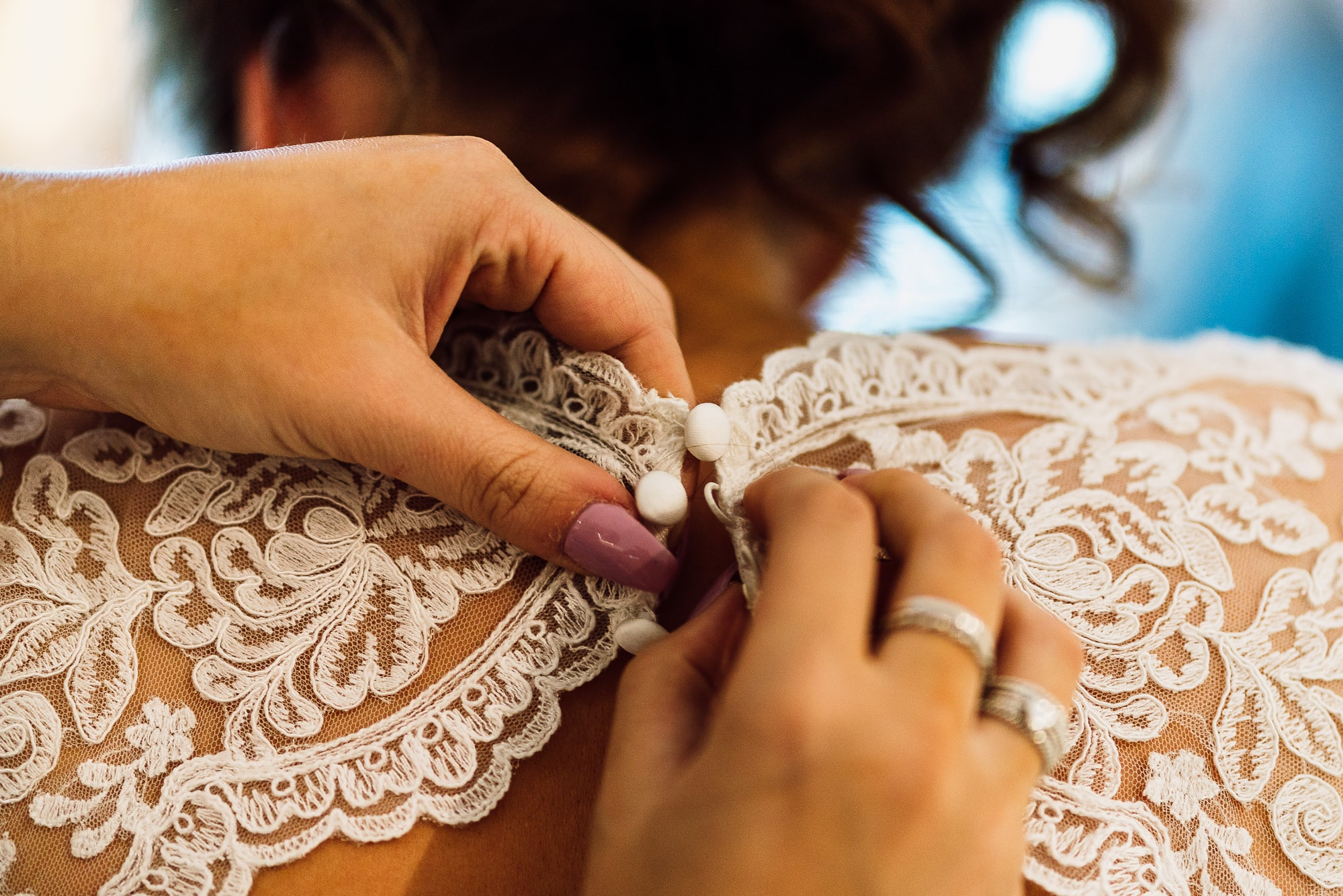 Bride having her dress done up at hilltop Country house