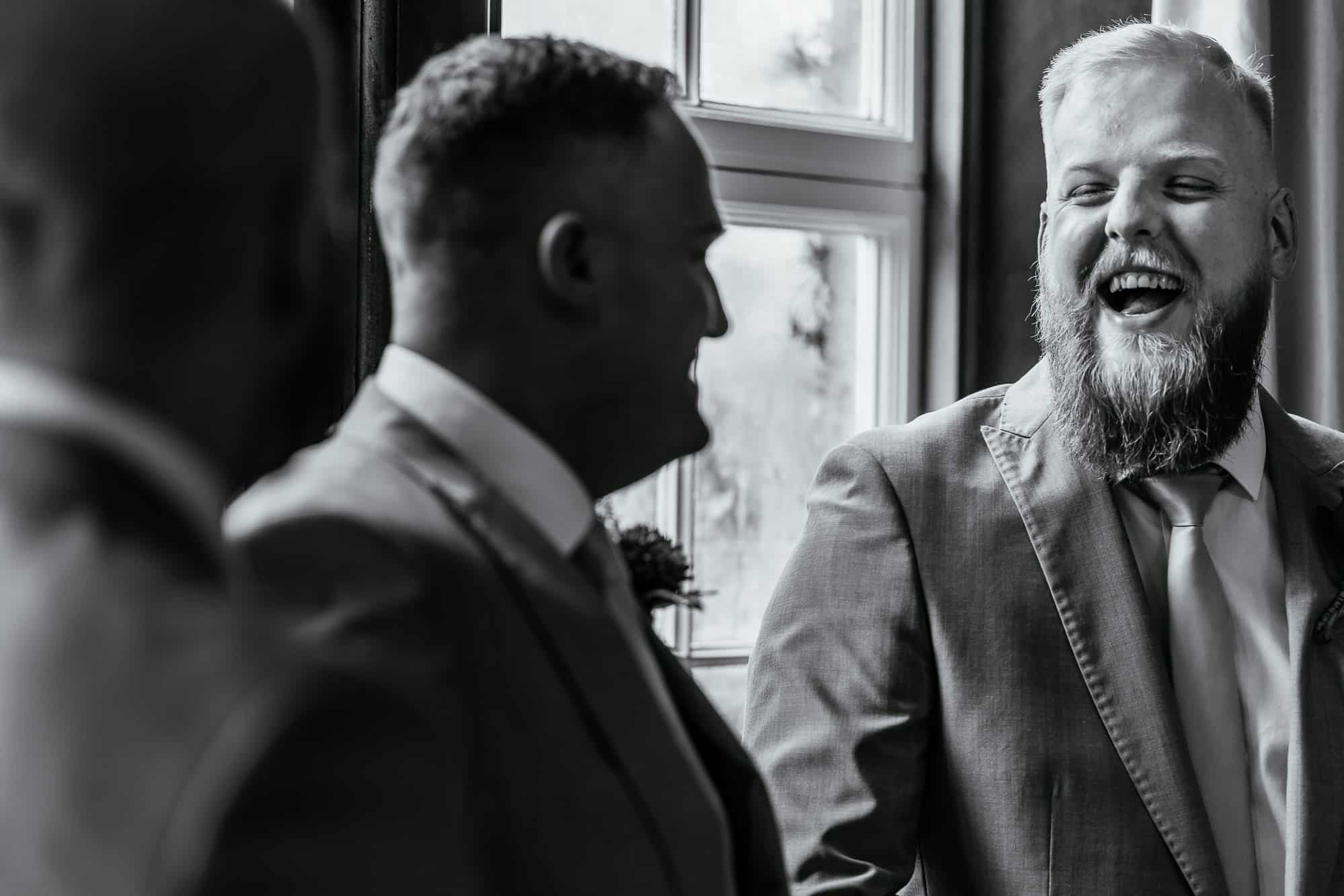 Best man and usher laughing before the service