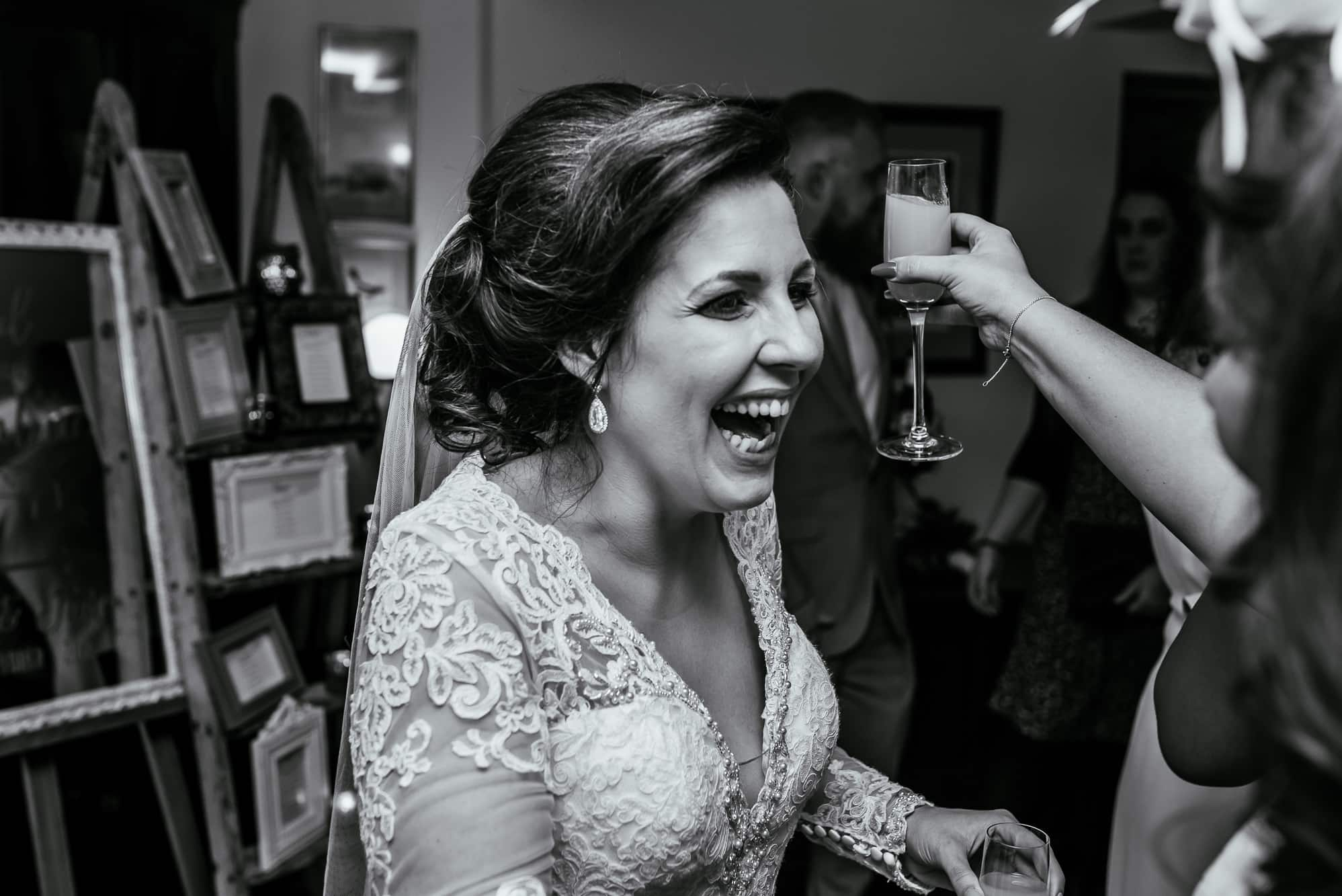 bride laughing at hilltop country house before hugging a guest