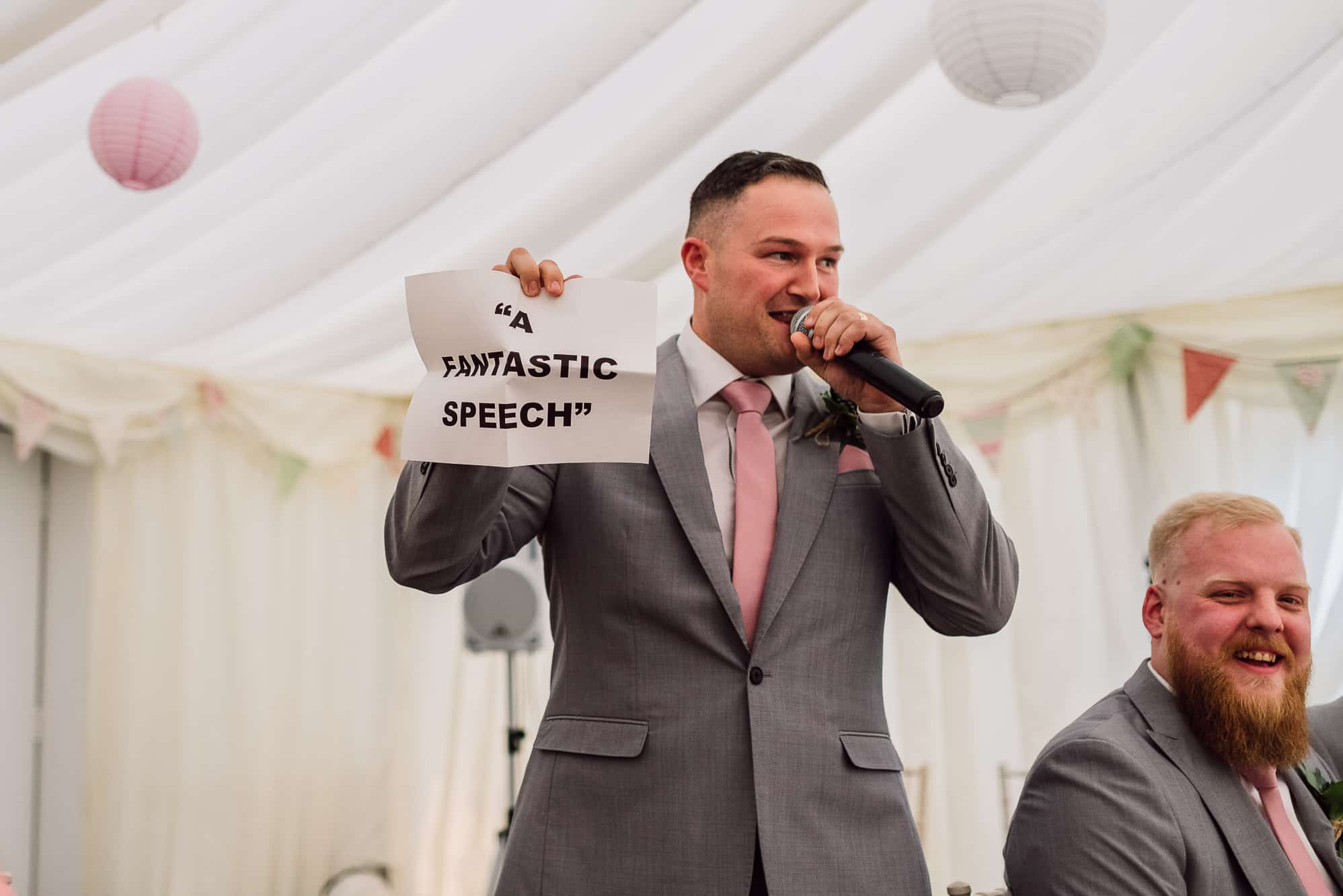 Best man holding up a sign saying this is a fantastic speech