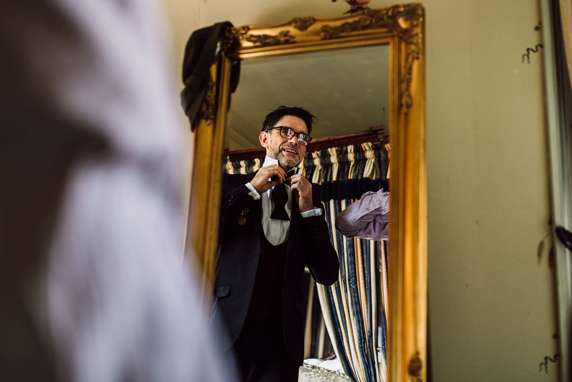 Groom getting ready whilst looking in the mirror