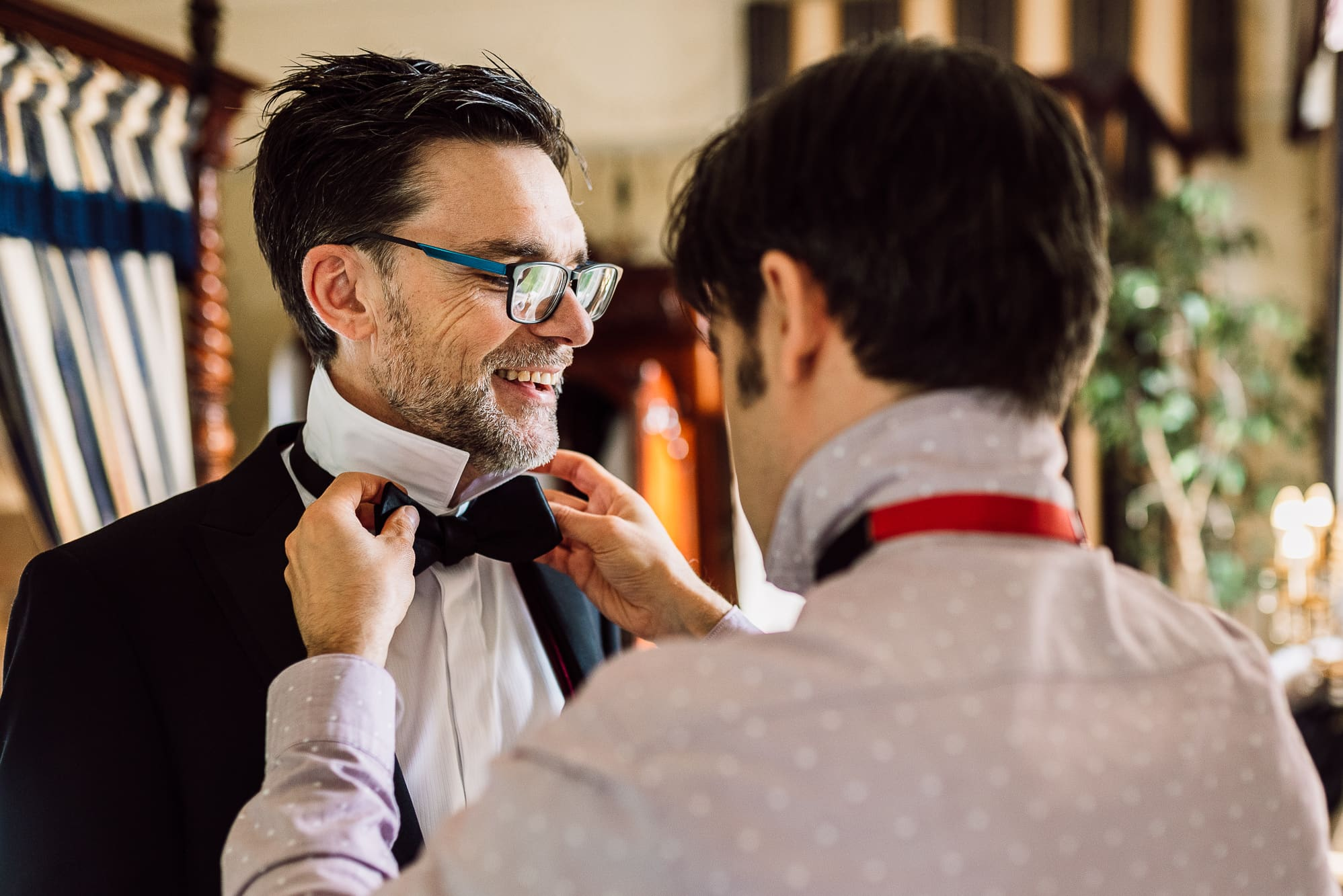 Groom helping his best man get dressed
