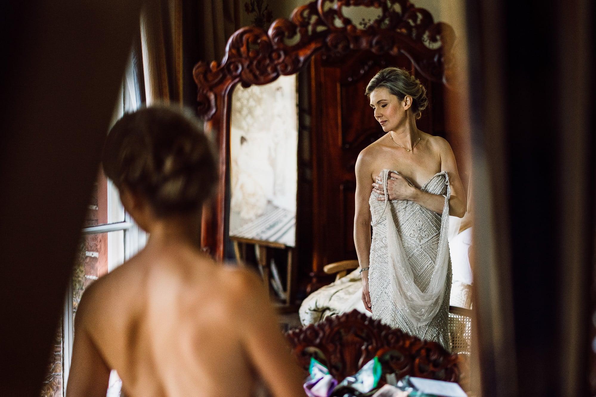 Bride putting her dress on at Trevor hall