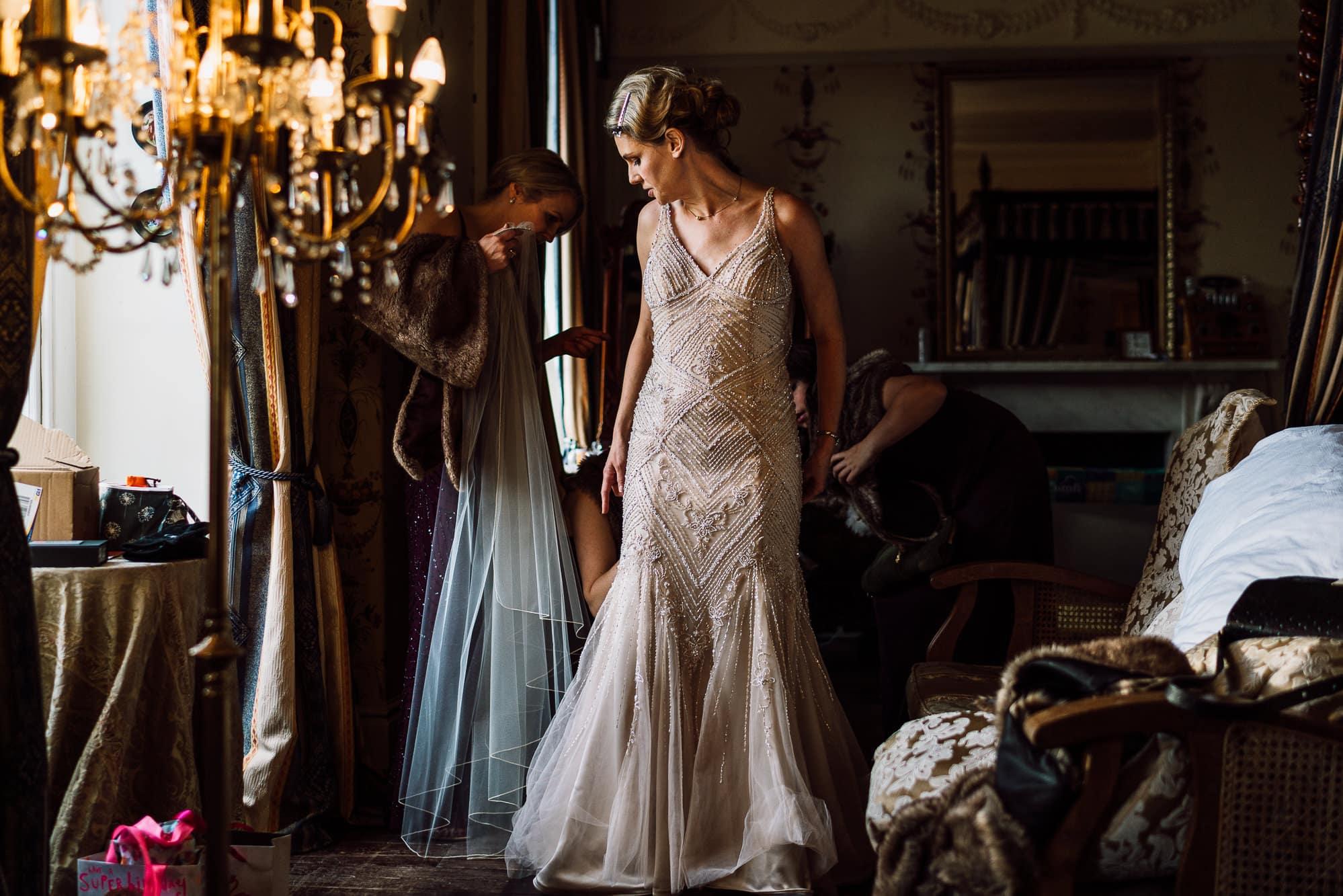 Bride putting on her dress at Trevor Hall
