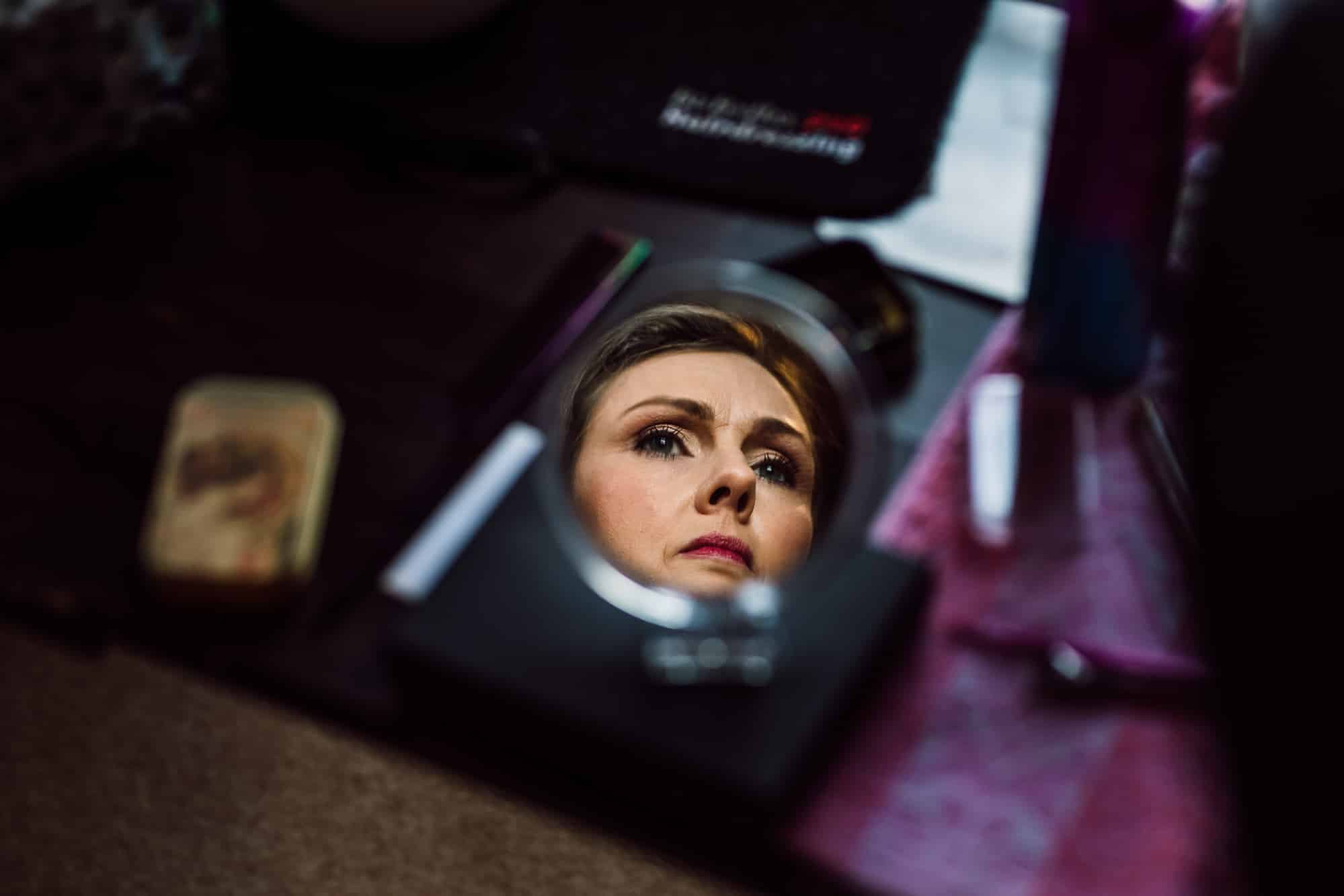 Reflection of the bride in a make up mirror