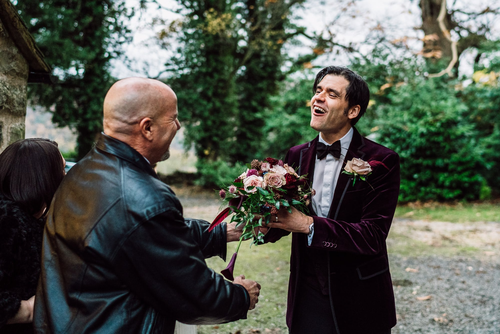 Groom taking flowers from a guest at Trevor Hall Church