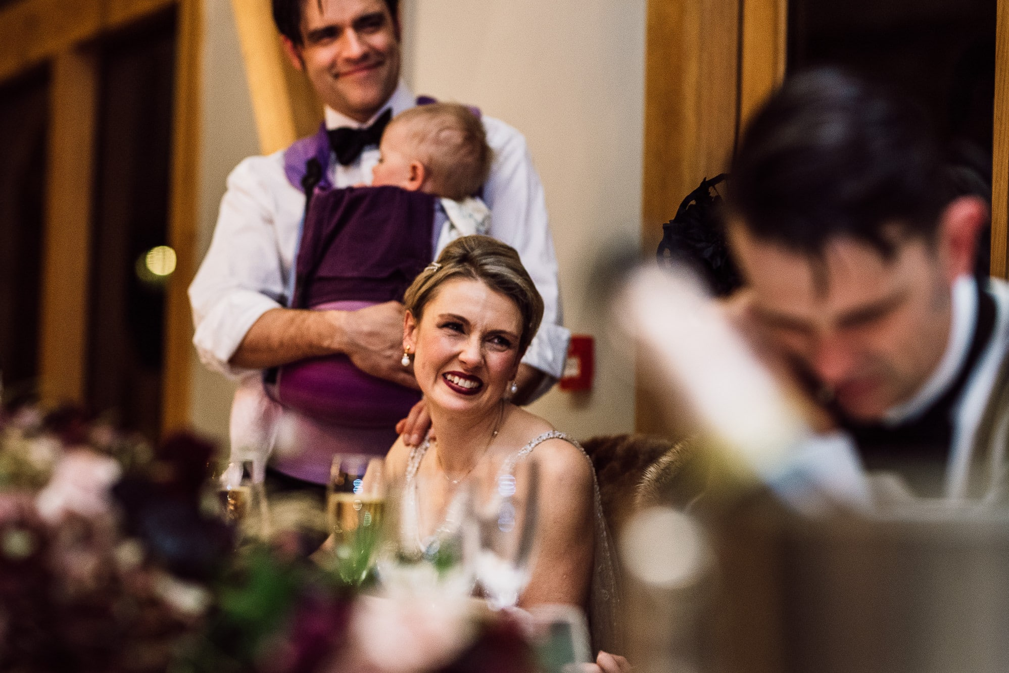 Bride laughing on top table during speeches at Tower Hill Barns