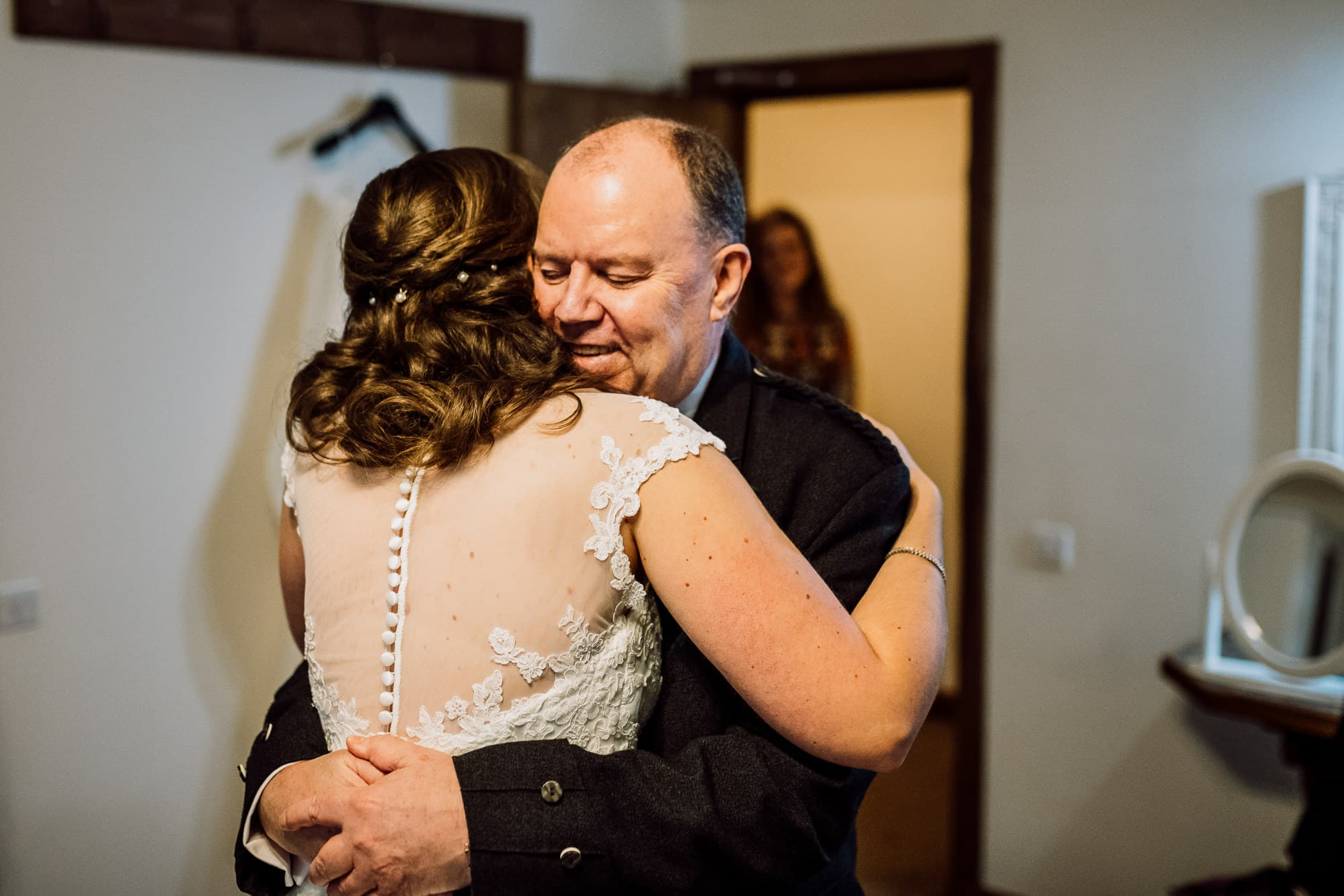 Father of the bride hugging the bride at Heaton House Farm
