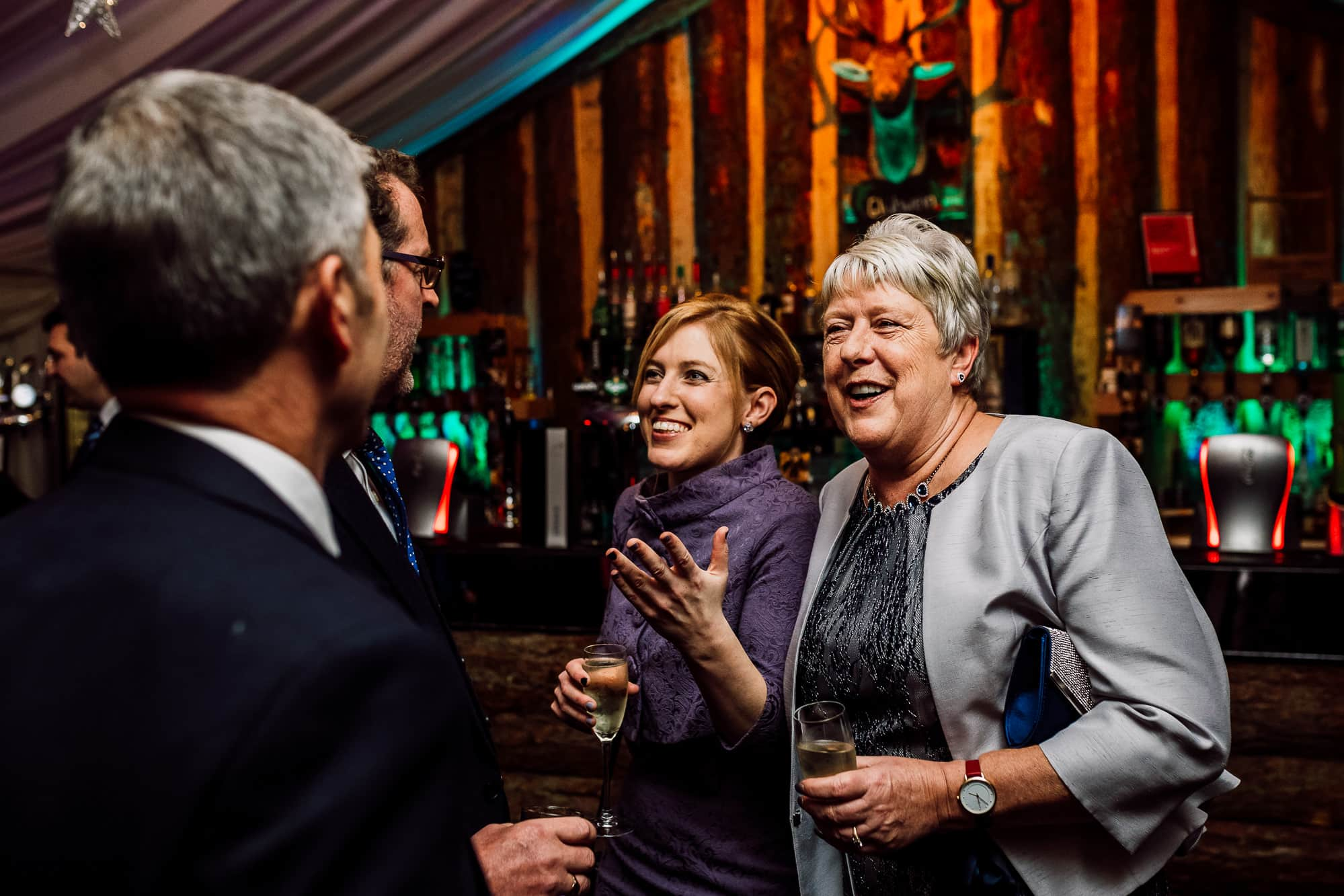 Guests laughing during reception drinks at Heaton House fARM
