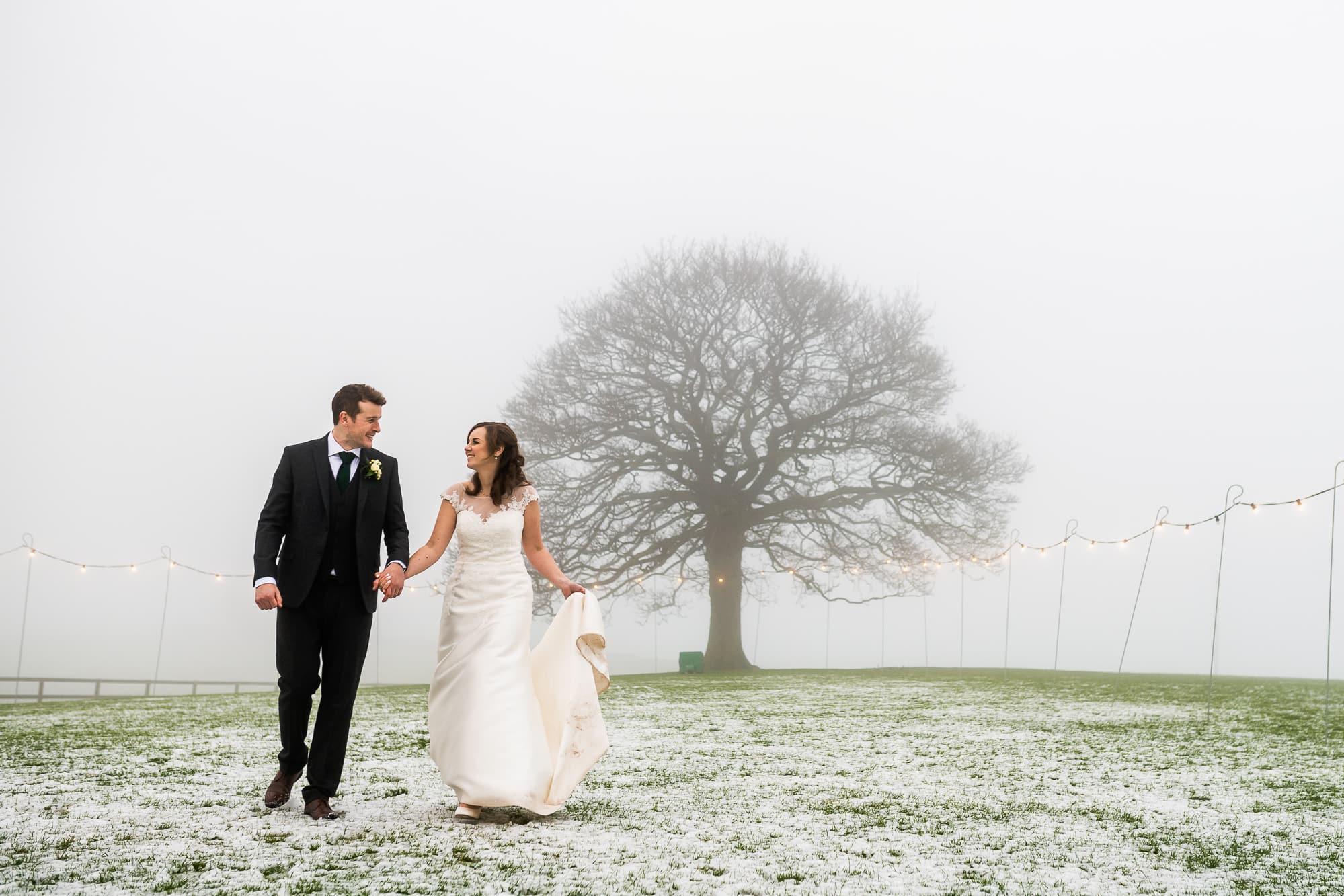 the newly weds walking in the field at Heaton House farm with the iconic tree behind