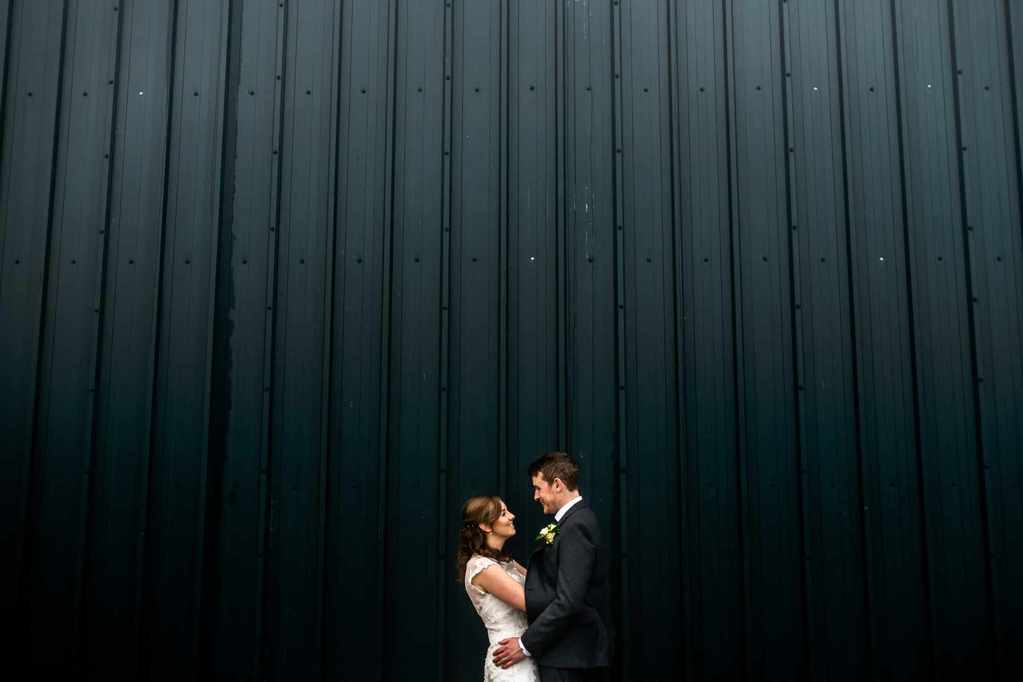 Bride and groom outside the barn at Heaton House farm