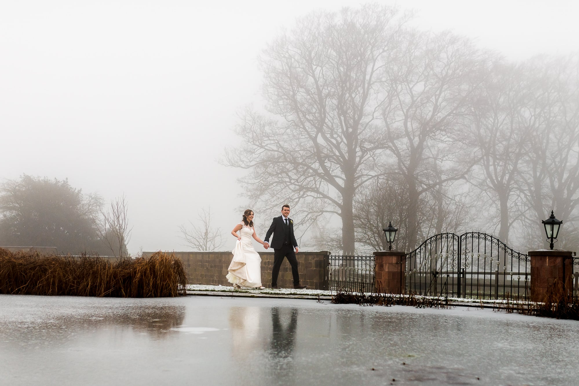 Bride and groom walking by a frozen lake at Heaton House Farm
