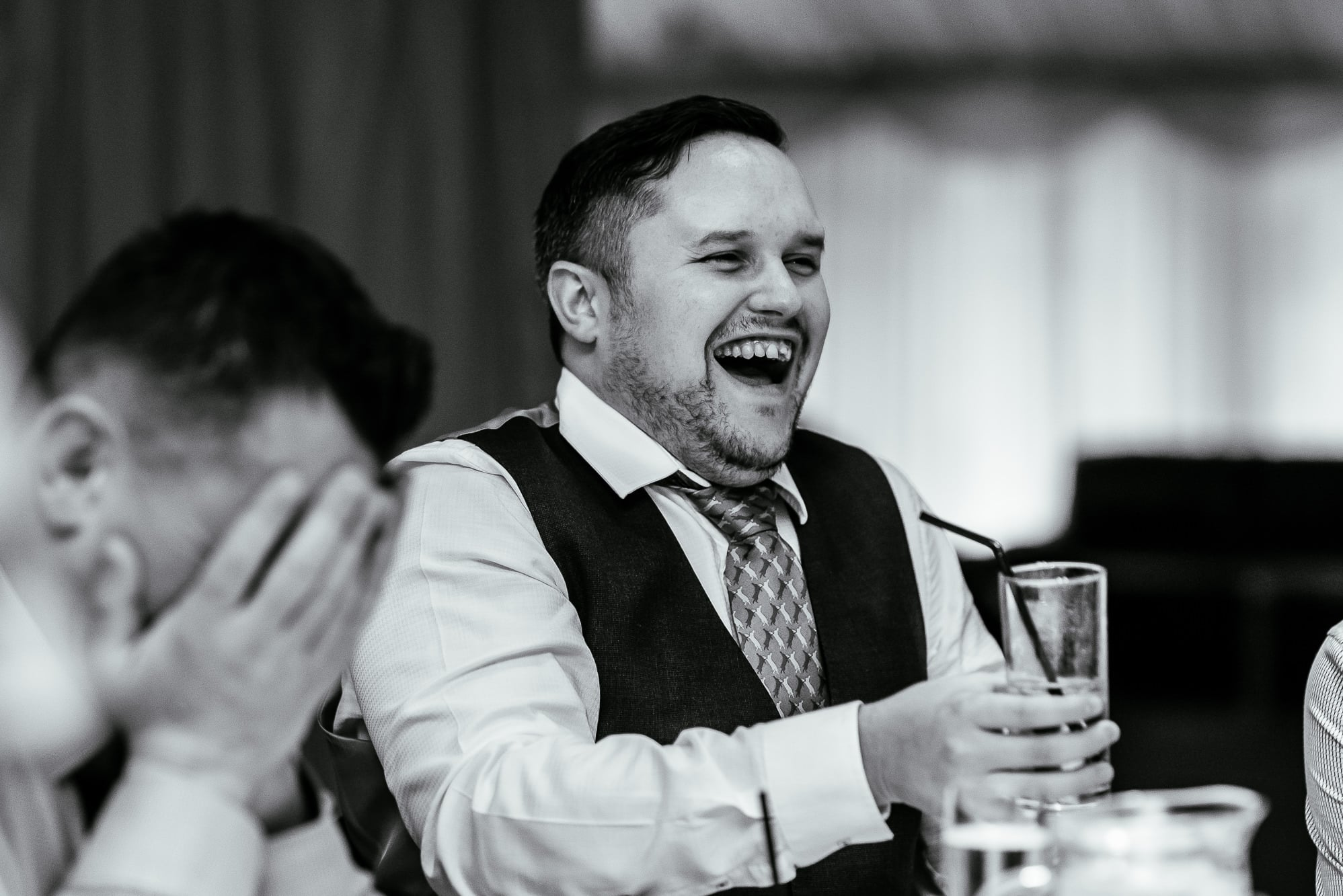 a male guest laughing at the speeches at Heaton House Farm