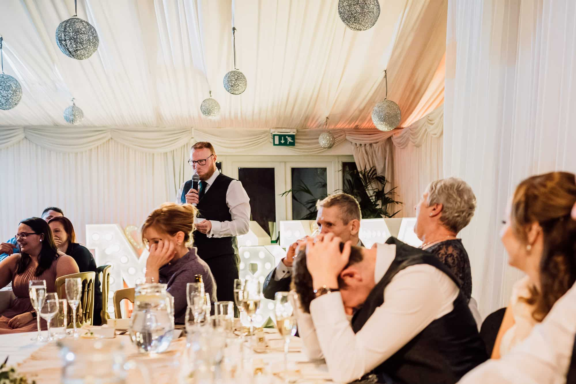 Best man speech at Heaton House farm whilst the groom holds his head