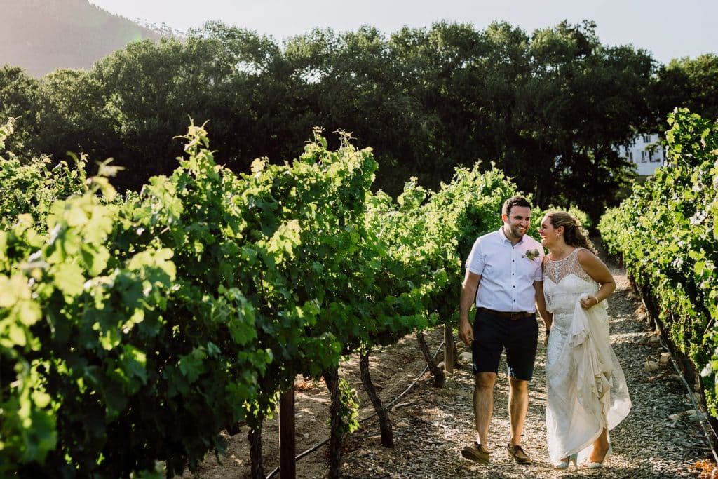Bride and groom walking through vineyards at Holden Manz