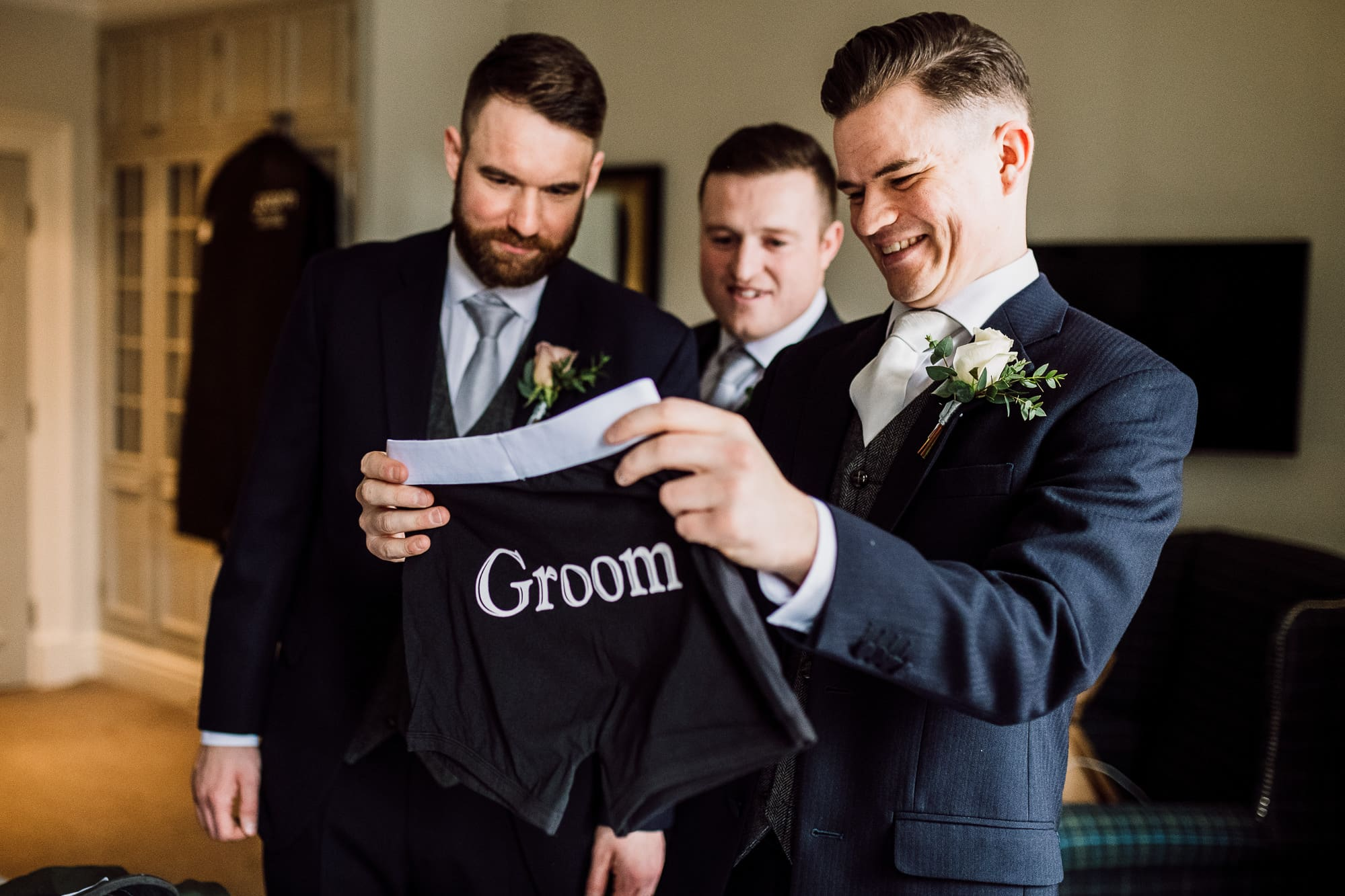 The groom opens up his gifts from his bride and is holding up some groom boxer shorts