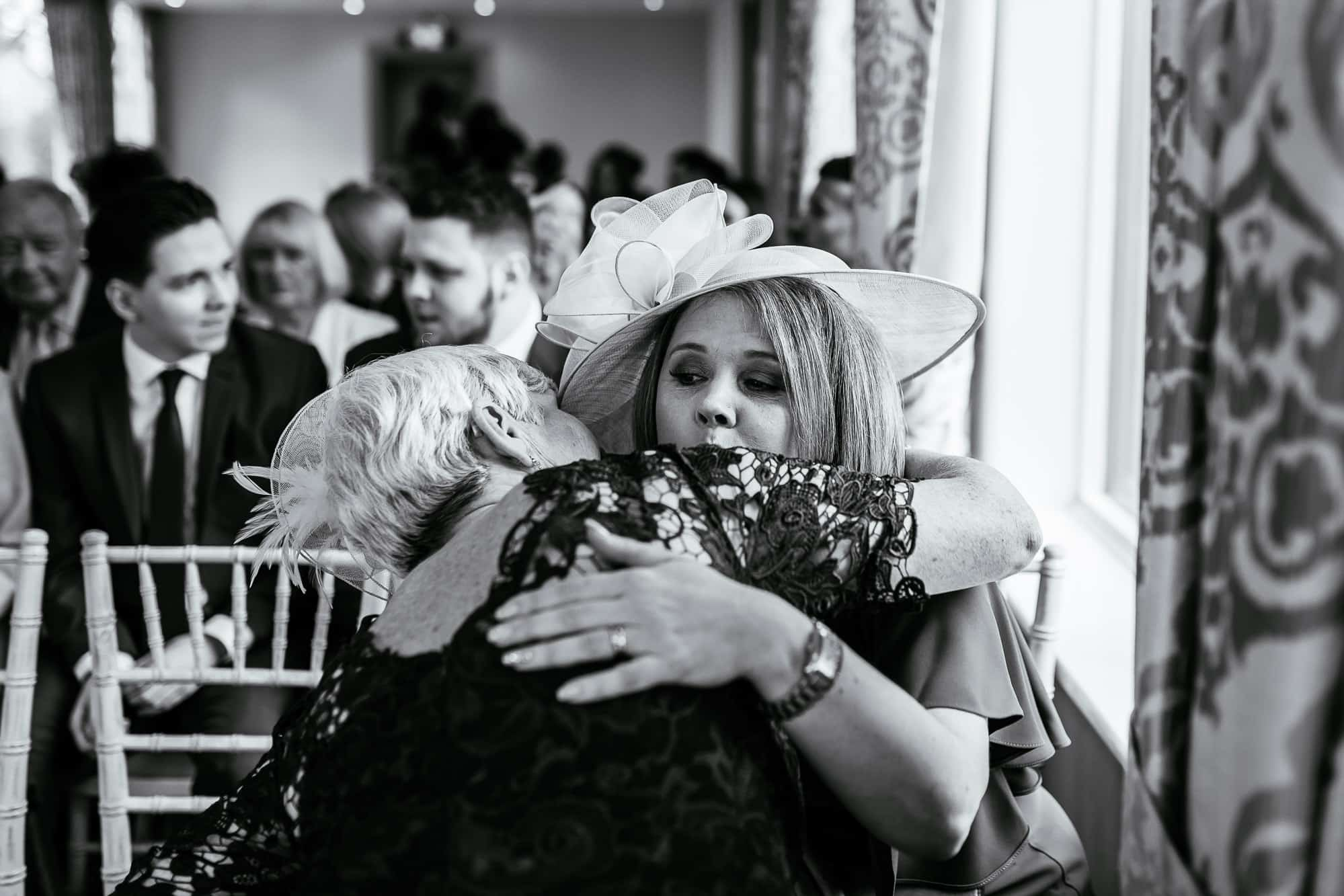 The two mothers of the couple hug before the ceremony at Crabwall Manor