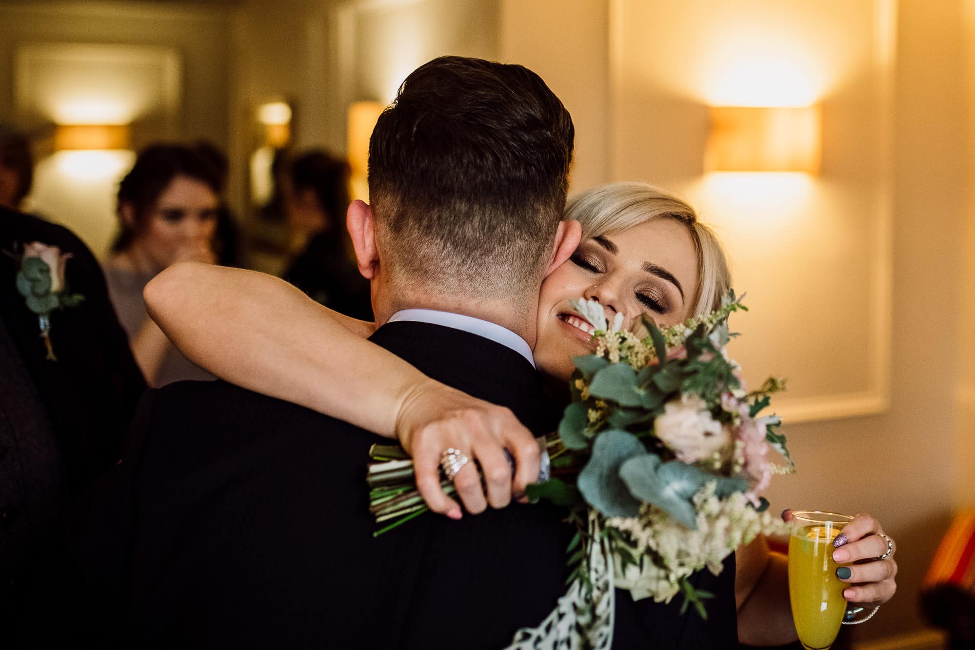 The groom is hugged by the bridesmaid during reception drinks