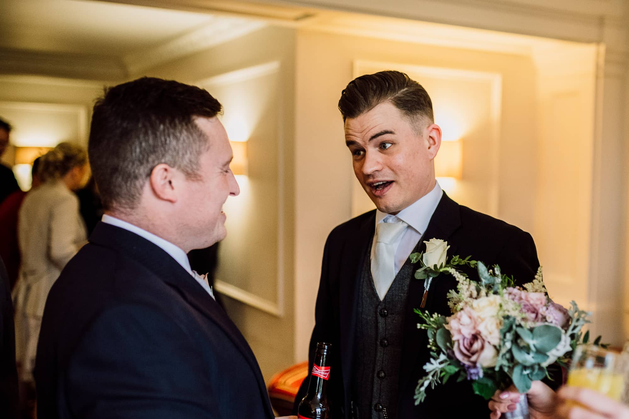 Groom is talking to his usher during reception drinks