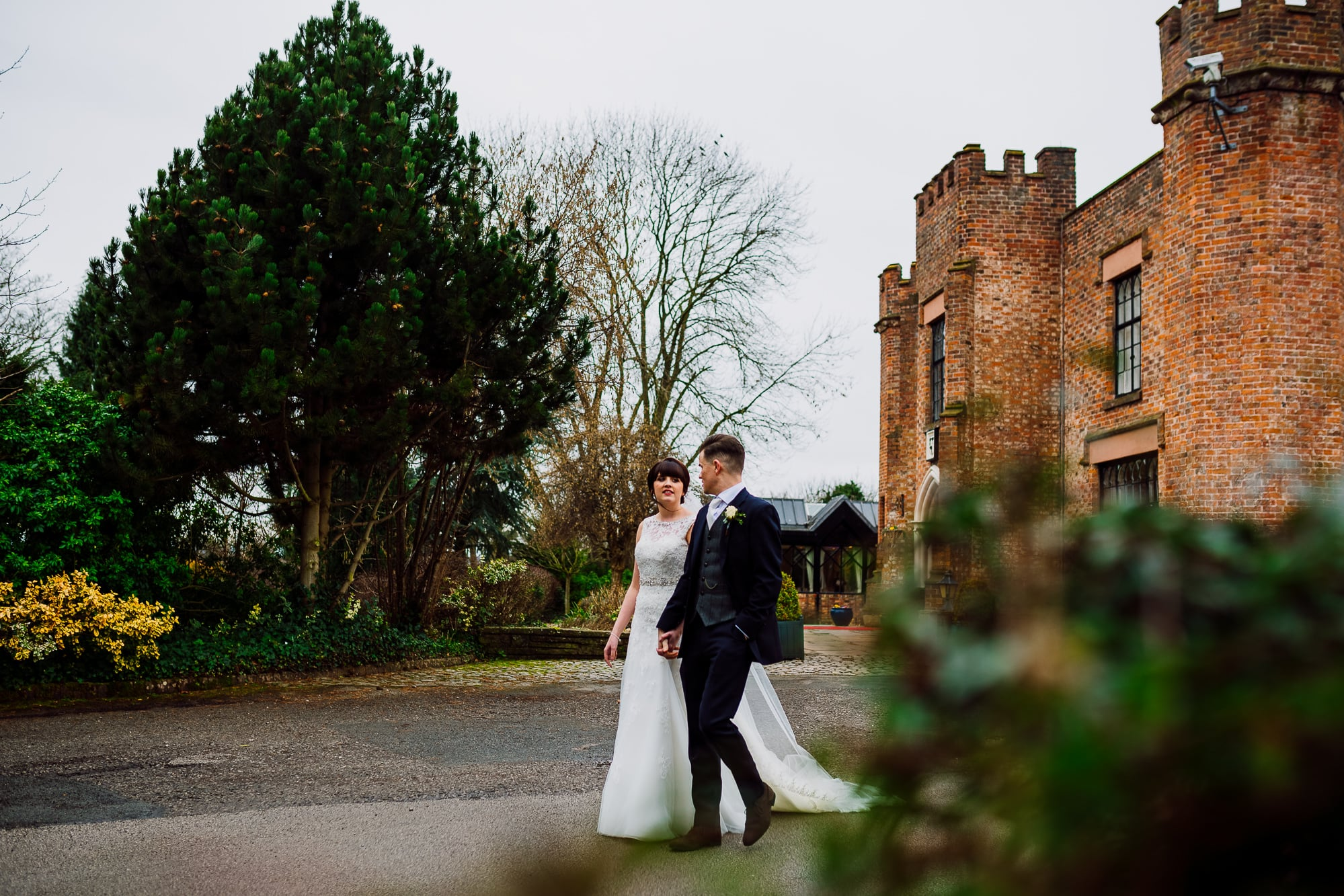 he bride and groom walk away form Crabwall Manor during couples portraits