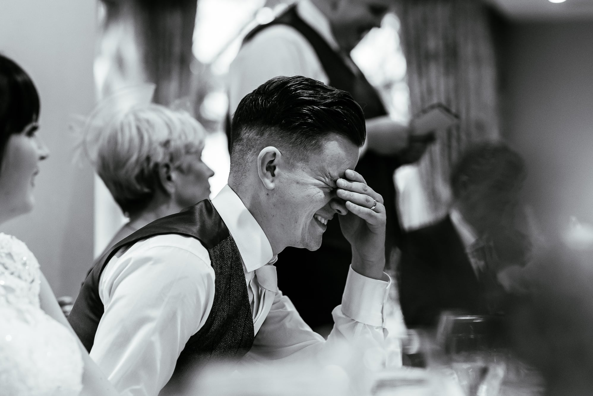 Groom holds his head as the best man speaks behind him