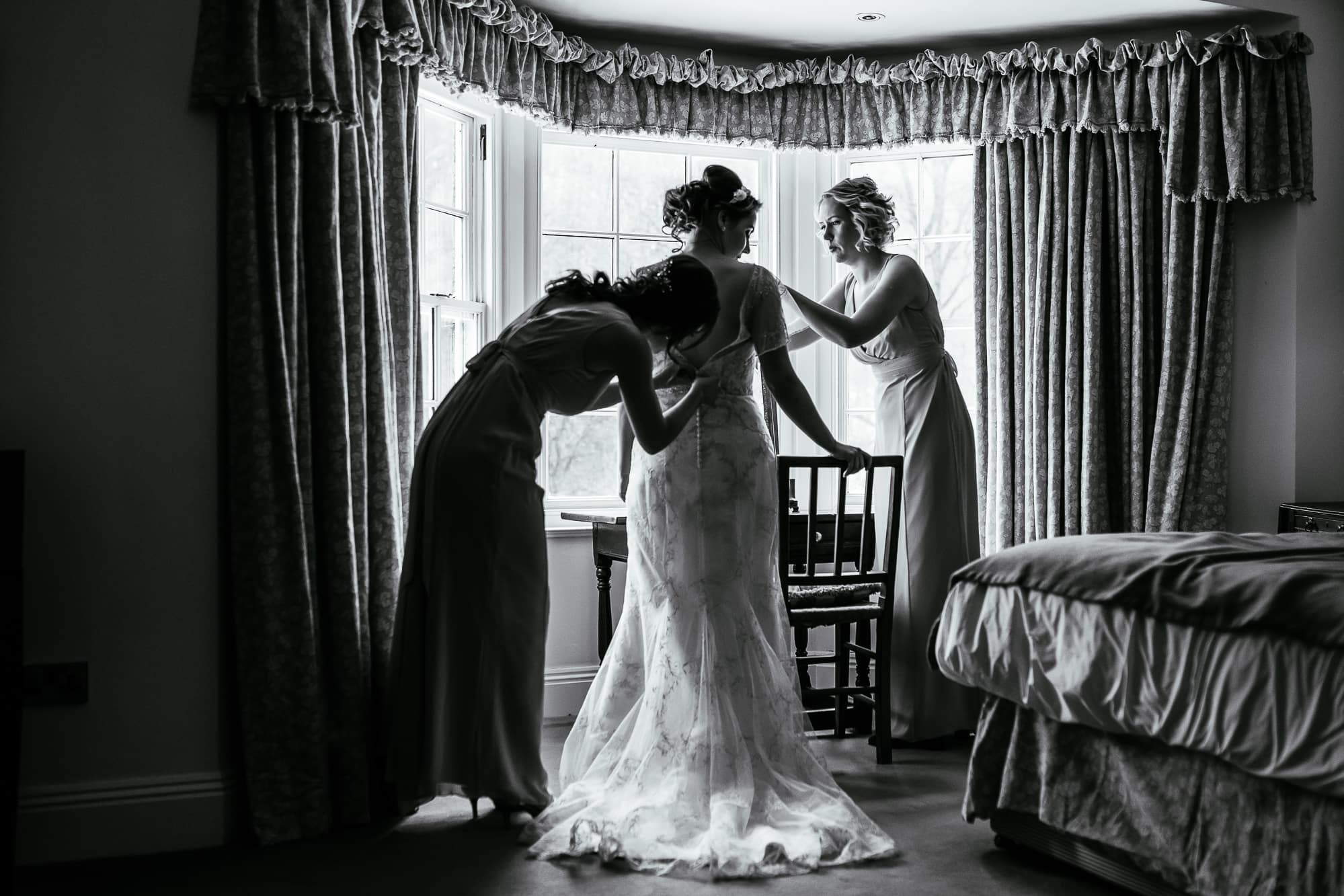 The bride getting into her dress and being helped by her bridesmaids
