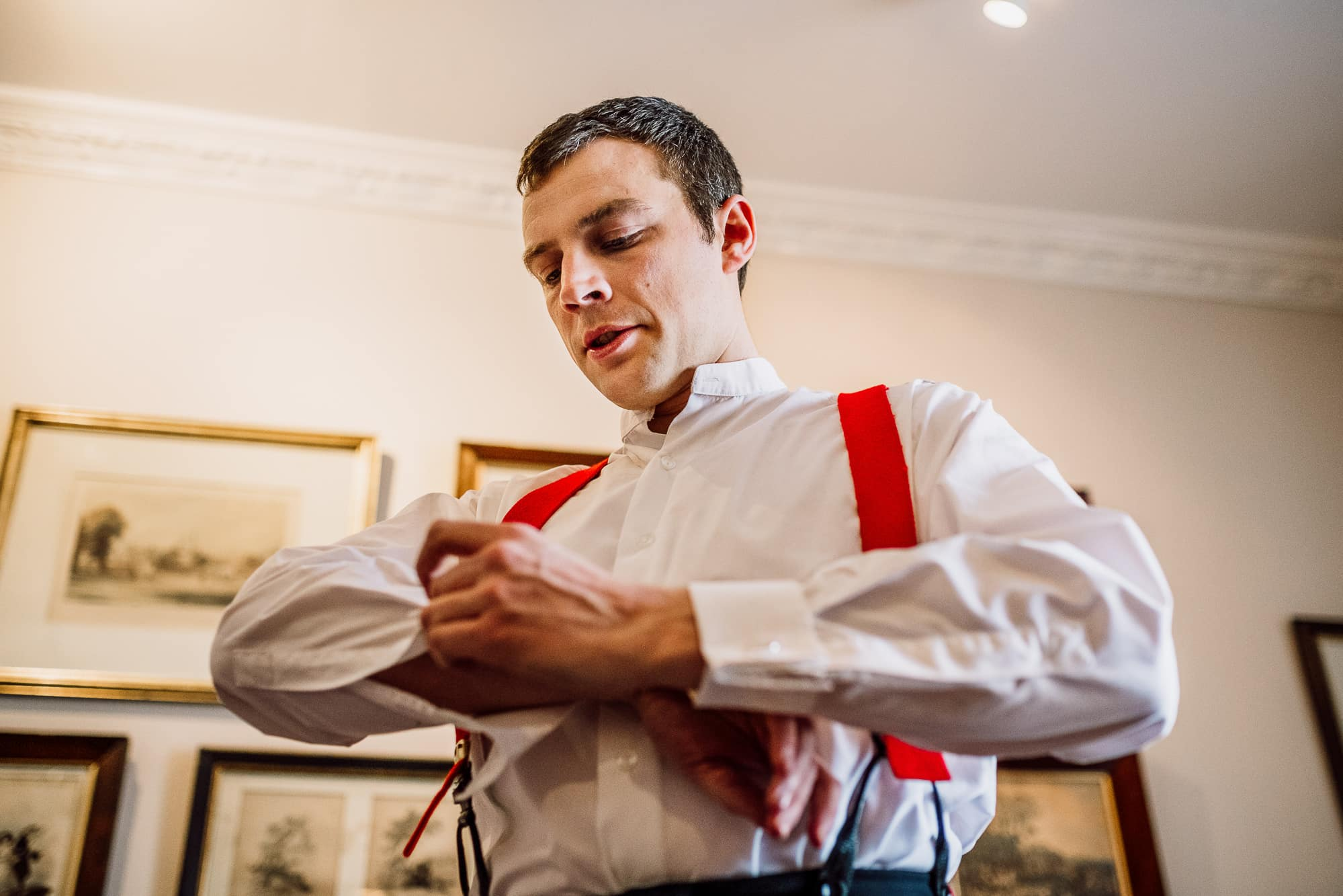 The groom getting dressed into his army uniform at the Inn at Whitewell