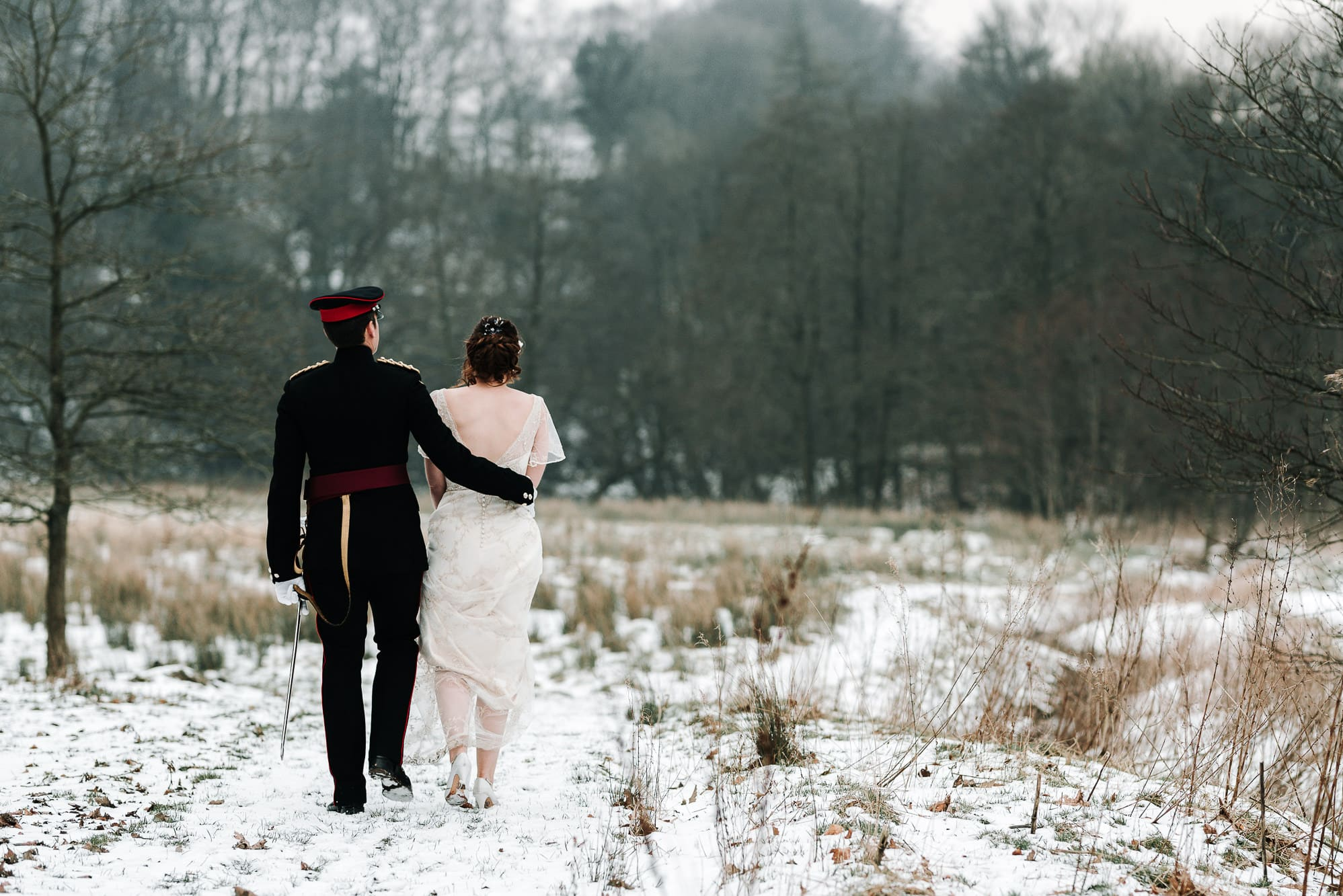 A photo from behind of the bride and groom walking in the snow