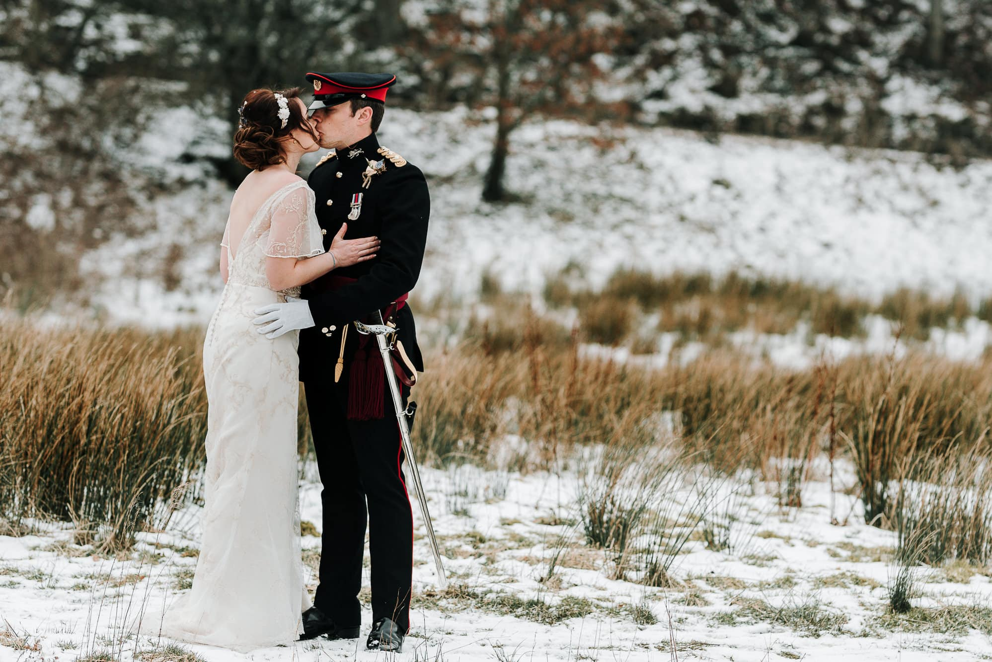 The newly weds kissing in the snow