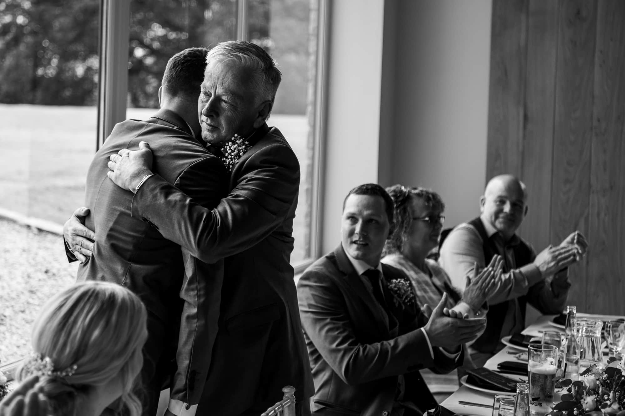 Groom and his dad cuddling after speeches