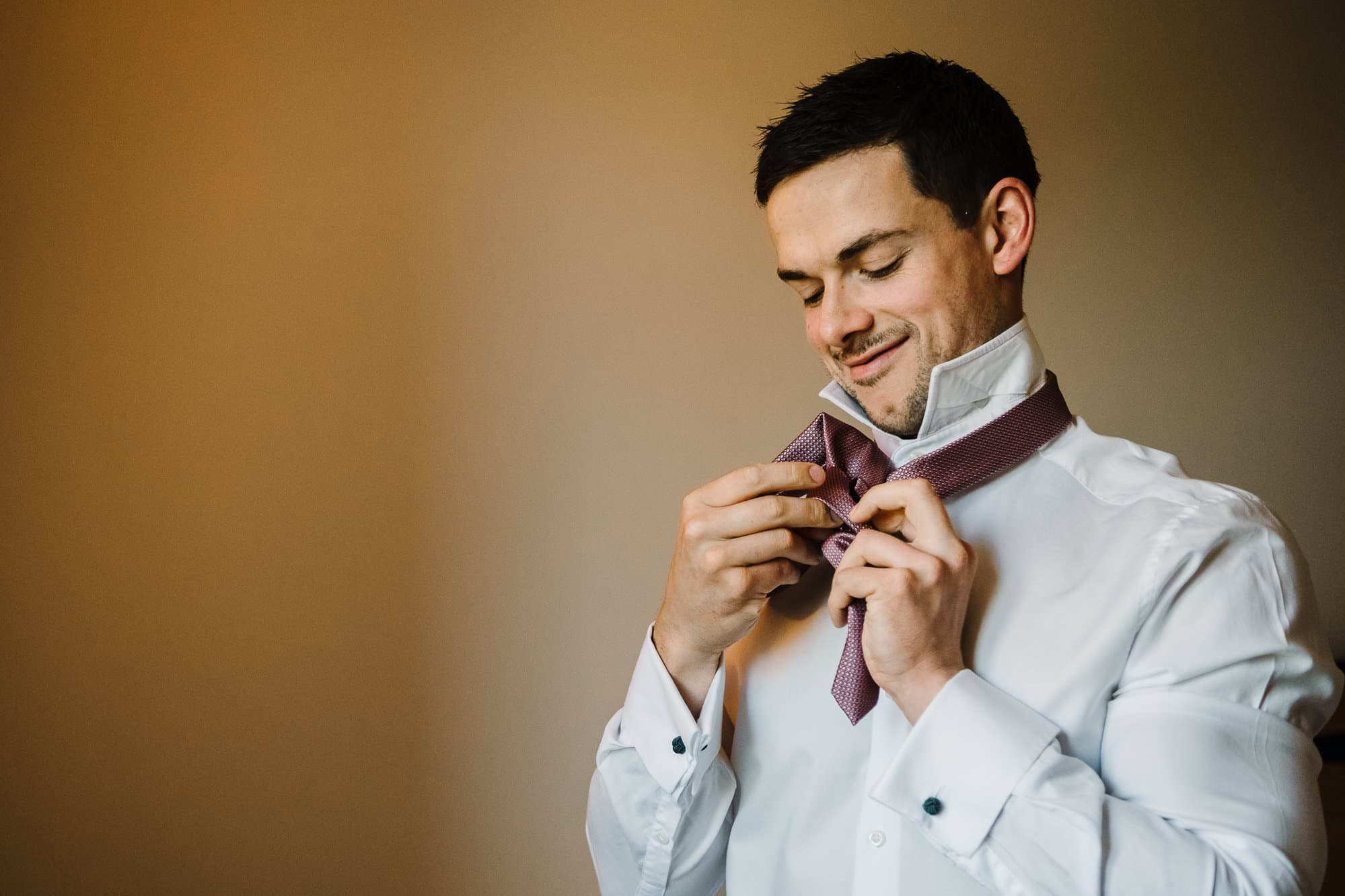 Groom putting on his tie
