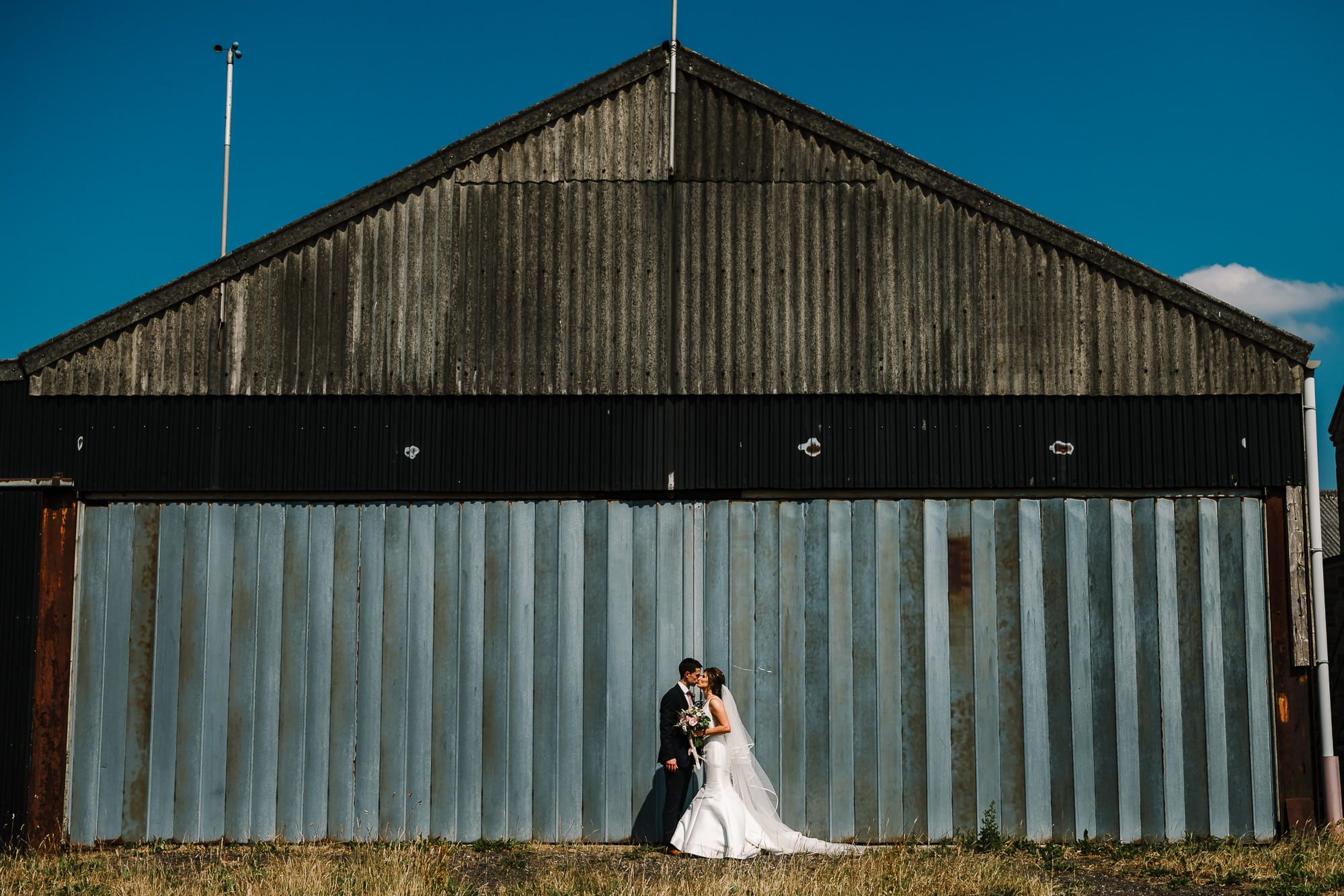 Bride and groom kissing outside a barn at Beeston Manor
