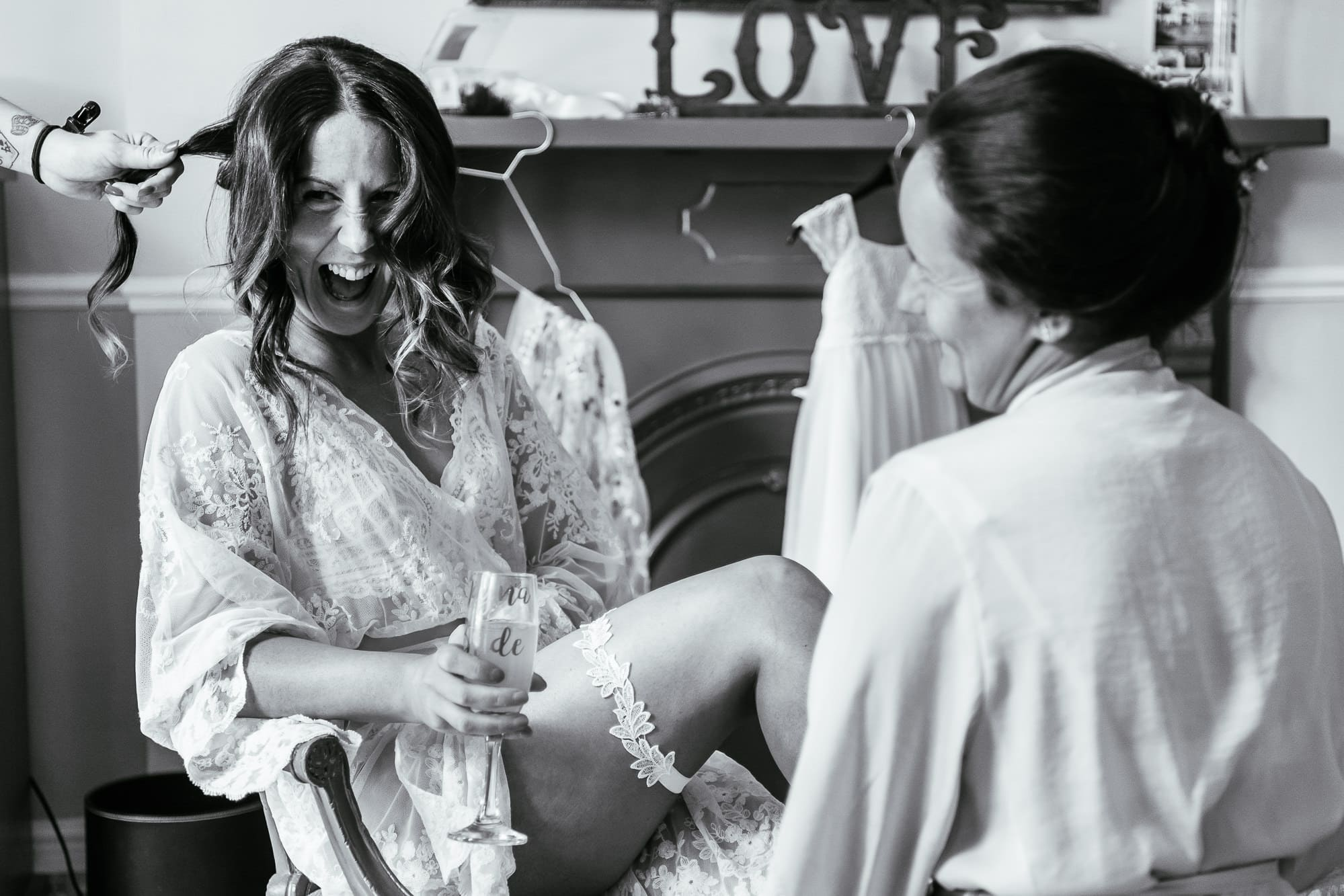 Photo of the bride putting on her garter and laughing