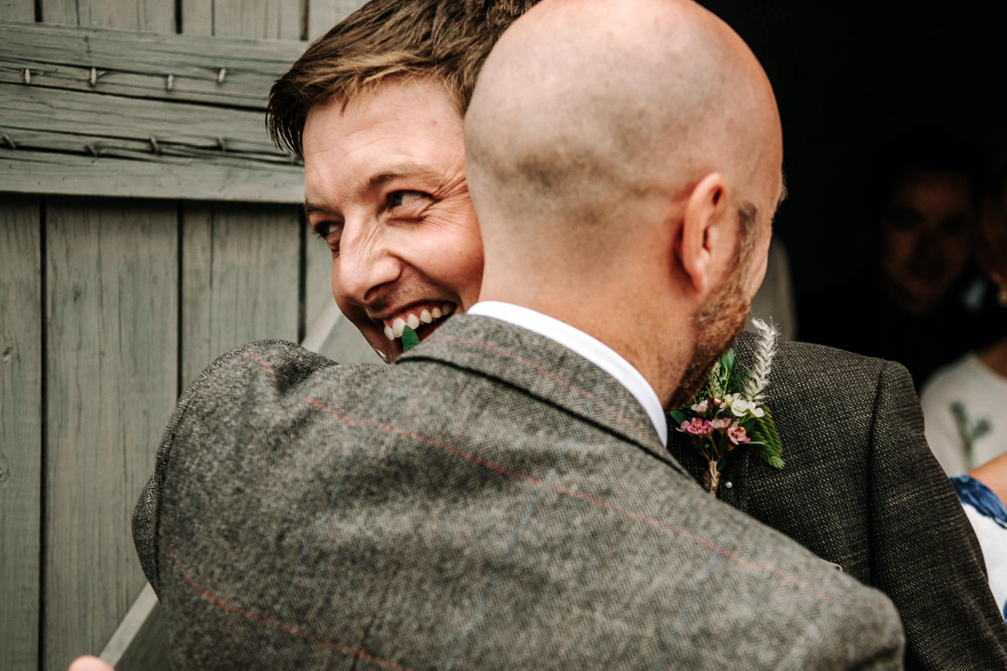 groom and best man hugging at stanford farm