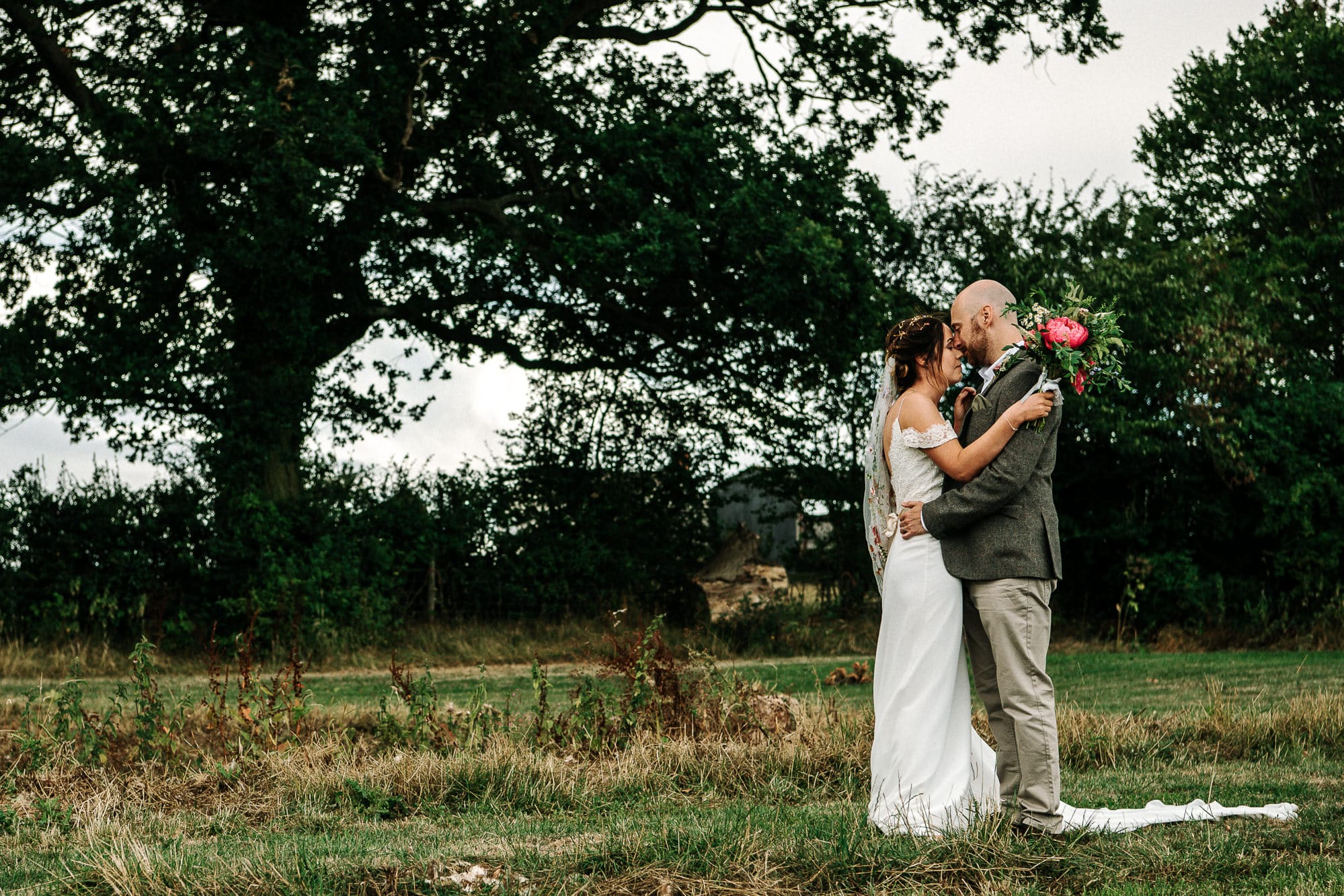 Bride and groom cuddling at Stanford farm