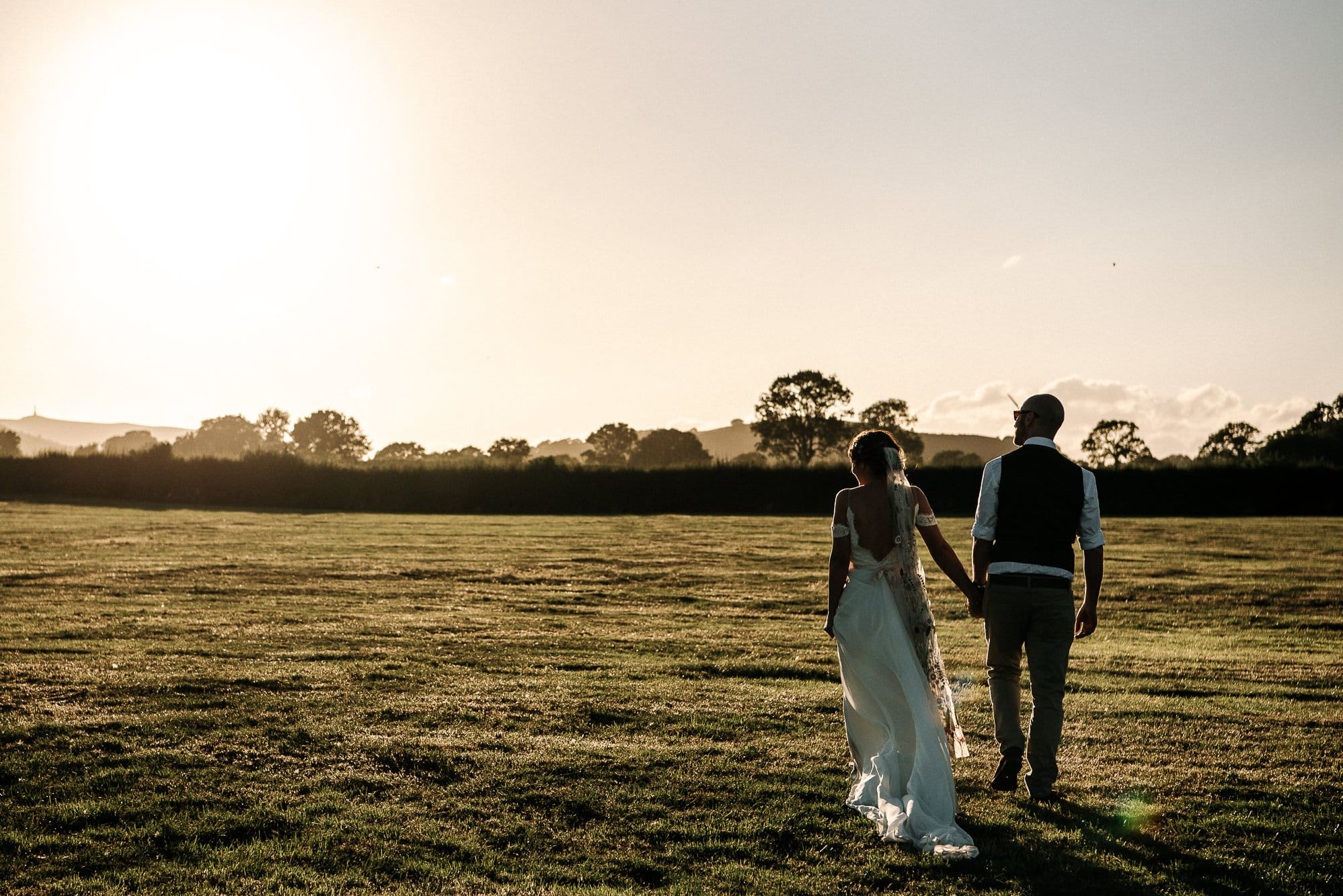 bride and groom walking at sunset at stanford farm