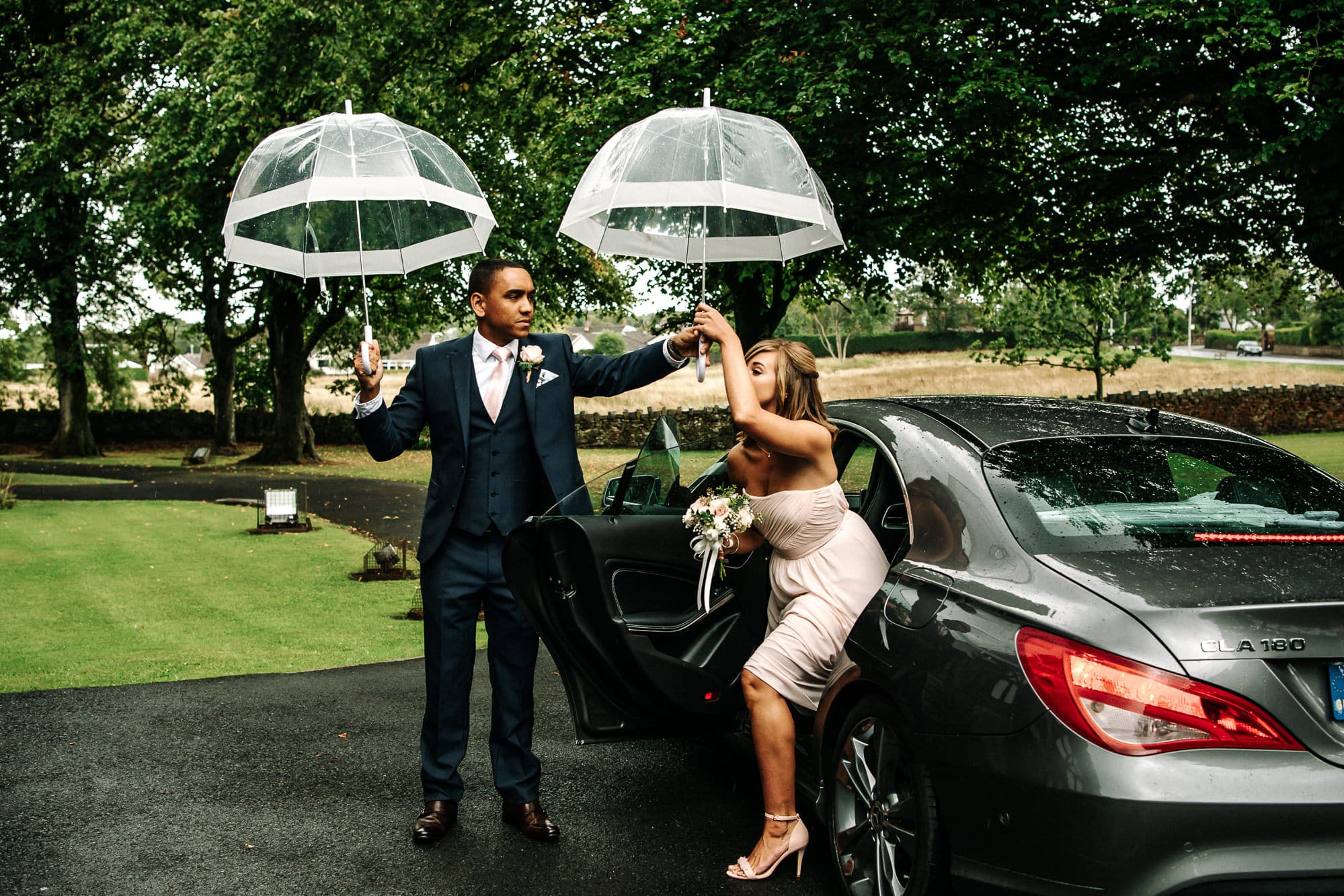 Bridesmaid getting out of the car with a brolly in the rain