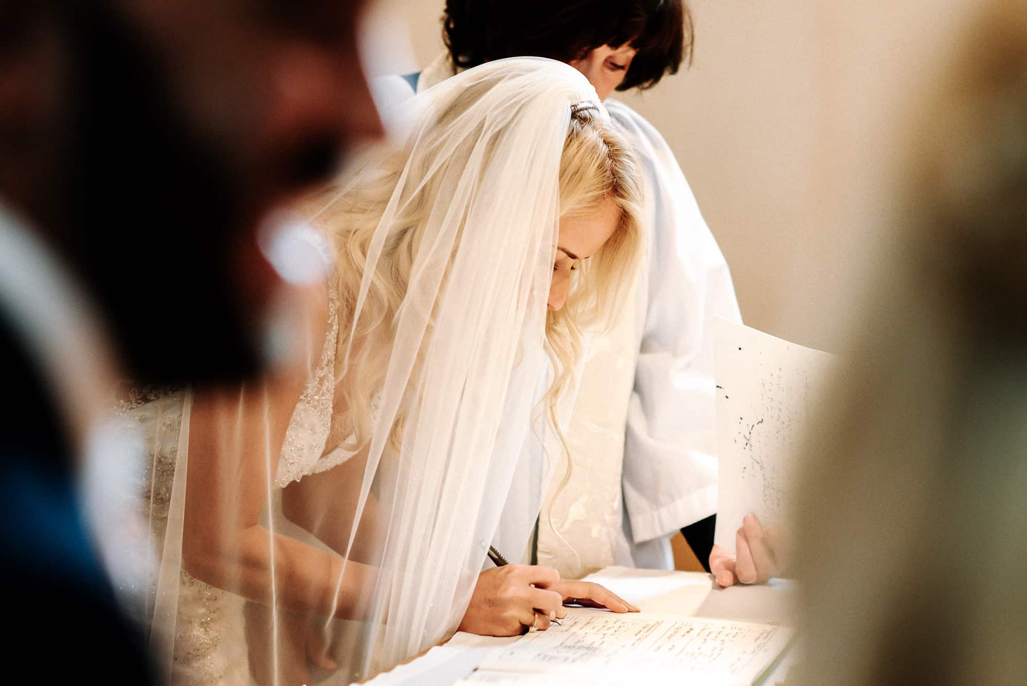 Bride signing the register in the church
