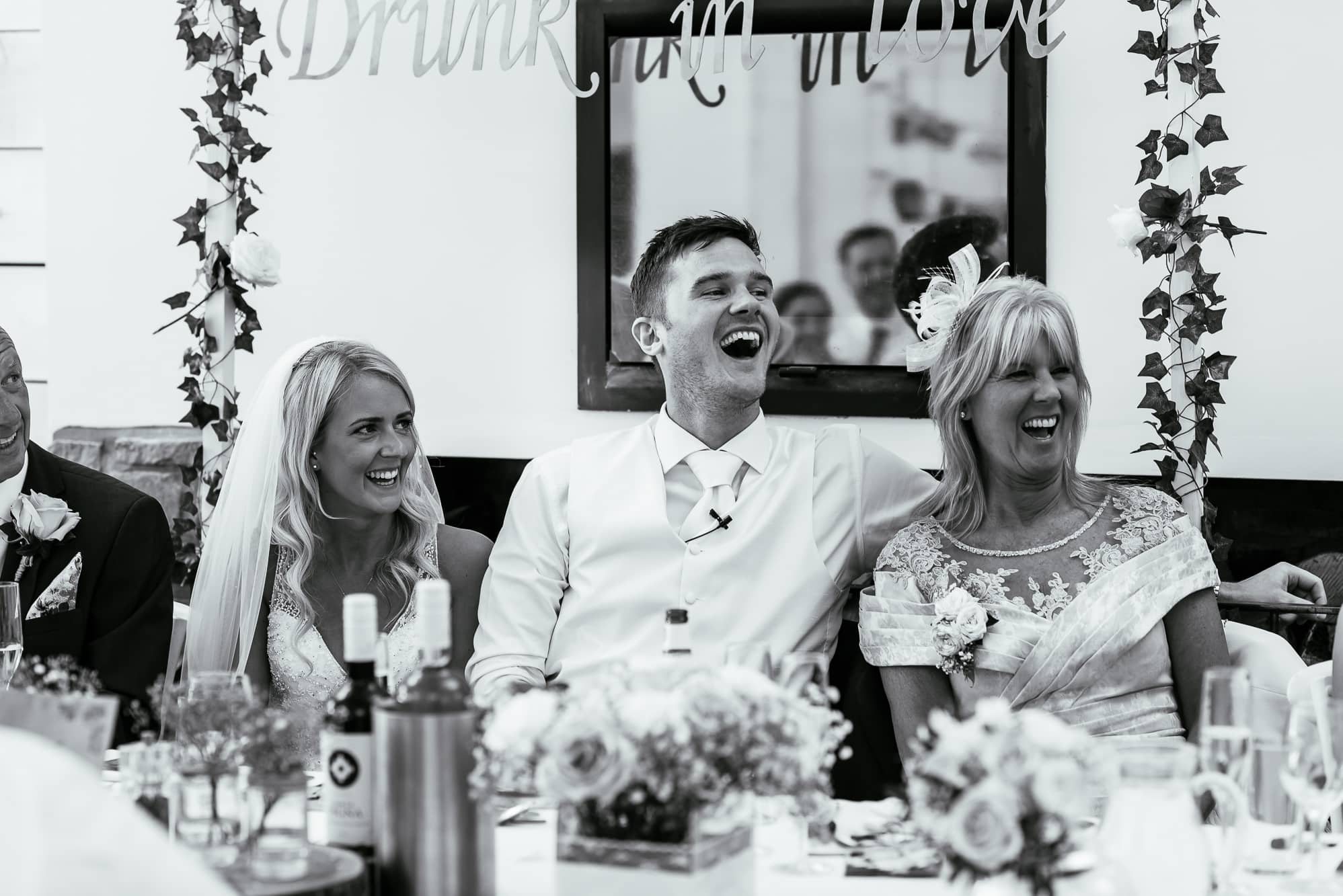 Groom and bride laughing during speeches
