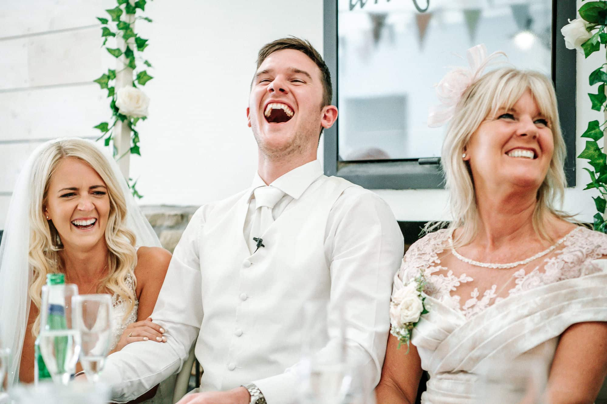 Groom laughing during speeches