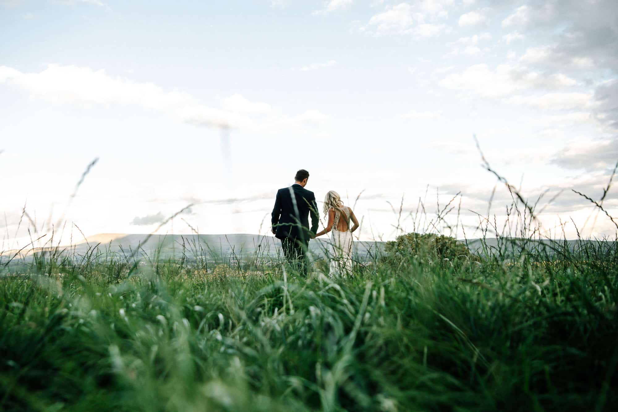 Bride and groom walking in a field at Bashall Barn looking over the Ribble valley