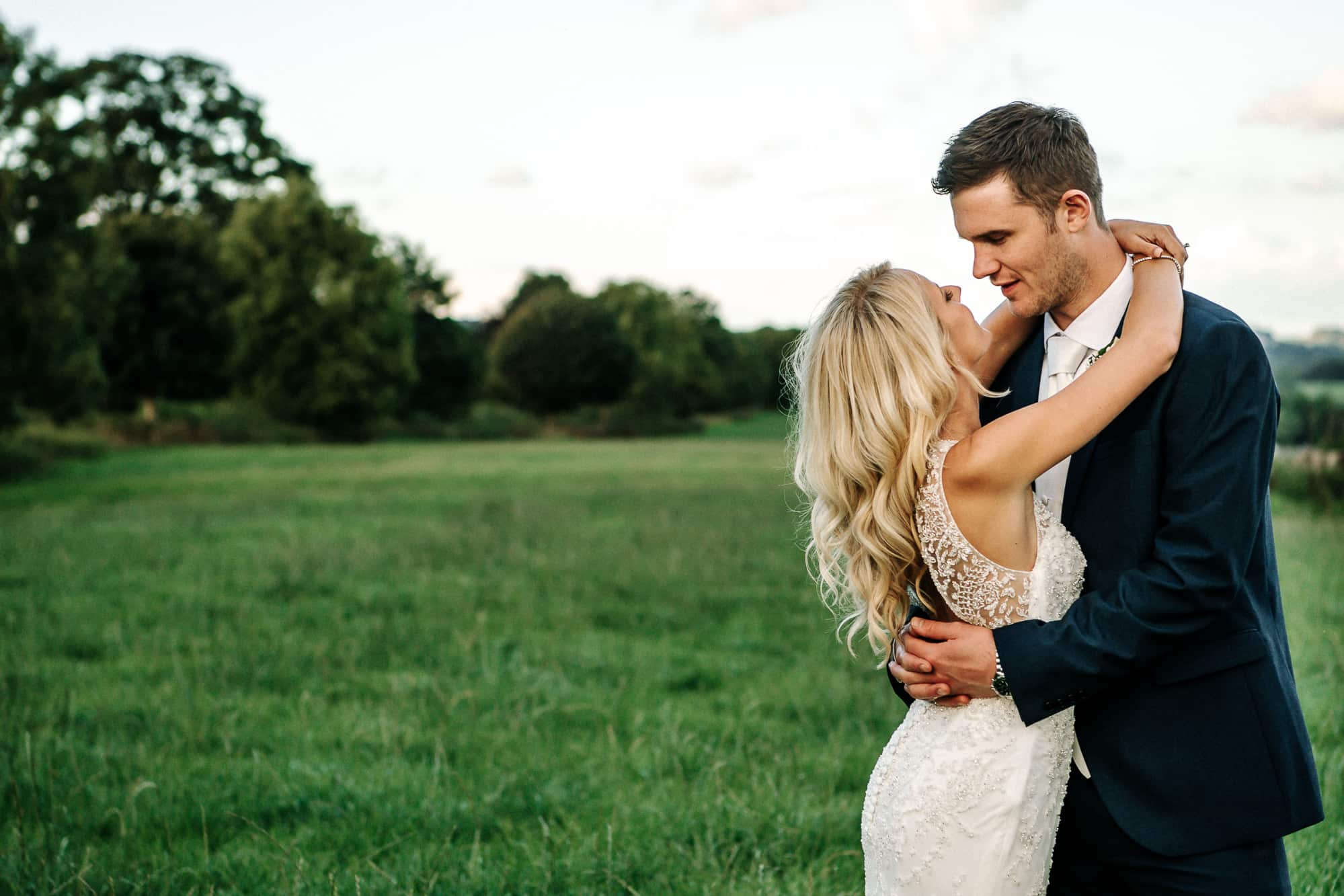 Bride and groom cuddling in the field at Bashall Barn